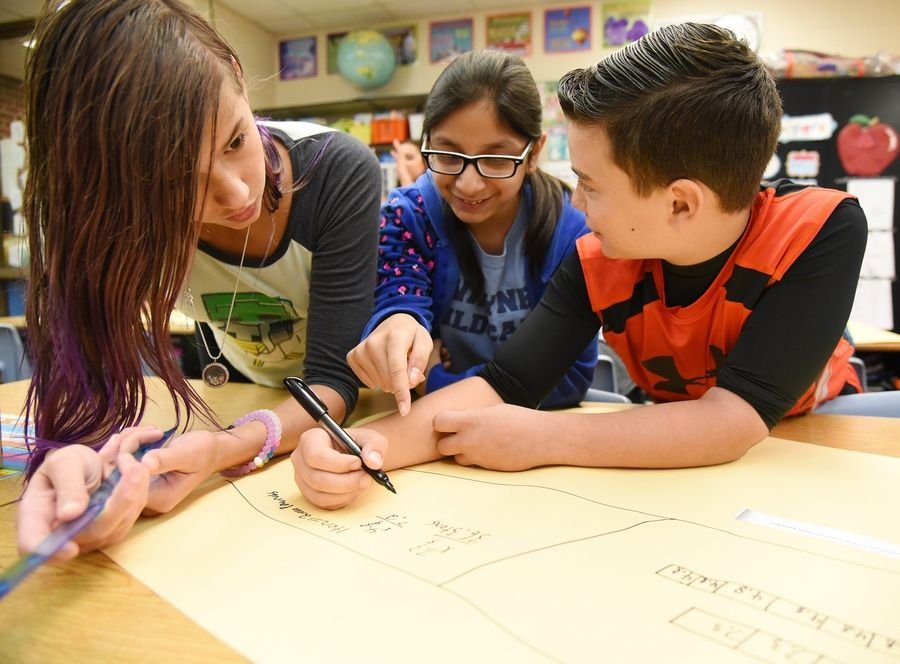 Fifth-graders Cece Welshimer, left, Amaani Ziauddin and Ari Kravis work on a group problem during math class at Wayne Elementary School Thursday.