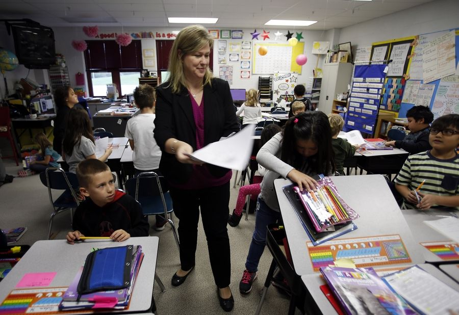 Kerry Sawyer hands out papers during a third-grade math class at Eastview Elementary School in Algonquin, where 64.6 percent of students are meeting/exceeding state standards.
