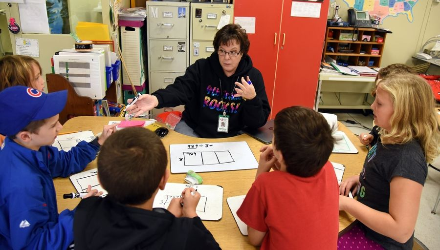 Fourth-grade math teacher Karen Mann works with students at H.C. Storm Elementary. Batavia elementary schools improved their meets/exceeds scores on state tests given this spring.