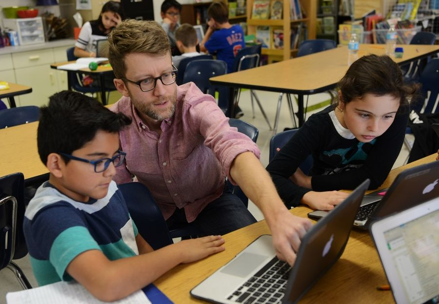 Fifth-grade math teacher Dan Cooper works with students Ernesto Perez, left, and Avery Rizzi at Forest Elementary School in Des Plaines -- one of four school showing dramatic improvement on state standardized test scores.