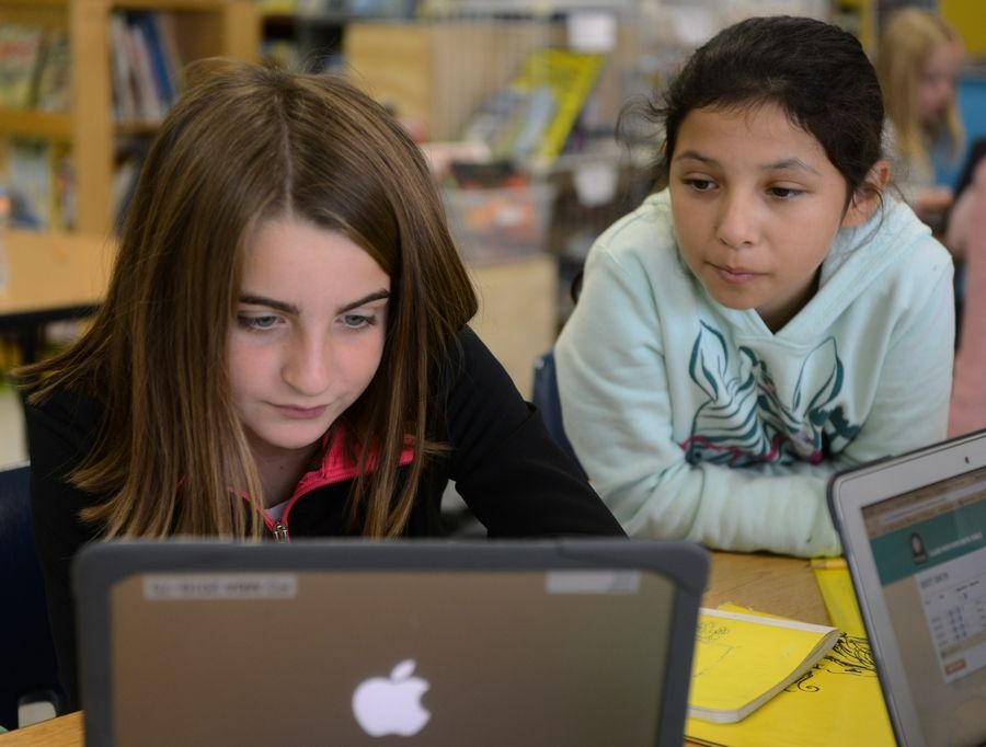 Fifth-graders Anna Cengel, left, and Adaliz Salazar work on math at Forest Elementary School in Des Plaines, where student test scores vaulted from 39.4 to 52.8 percent of students meeting or exceeding state standards.