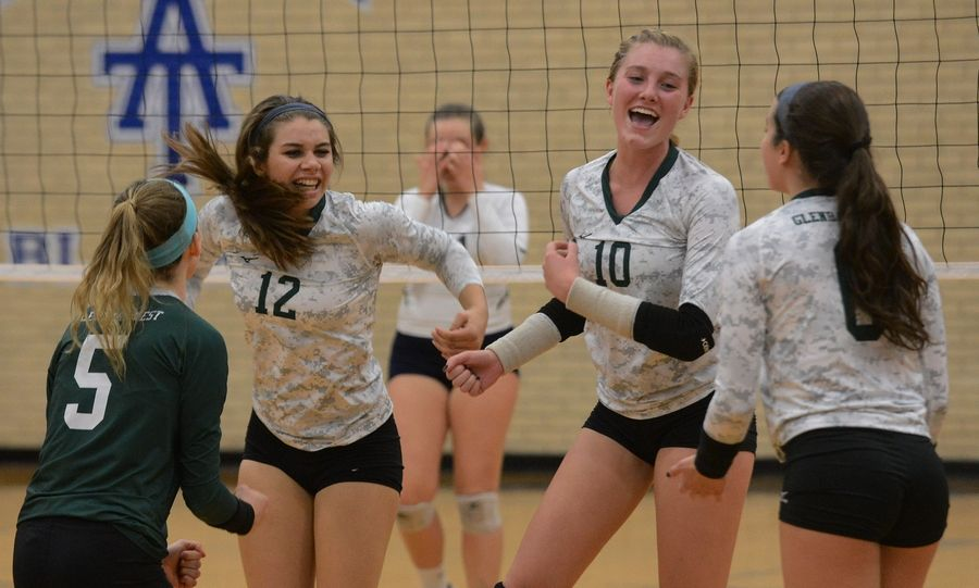 Glenbard West players including, from left, Clare Wagner, Nina Crawford, Ella Ridinger and Hannah Brodner celebrate their victory over Whitney Young during the Class 4A Addison Trail volleyball sectional semifinal Tuesday.