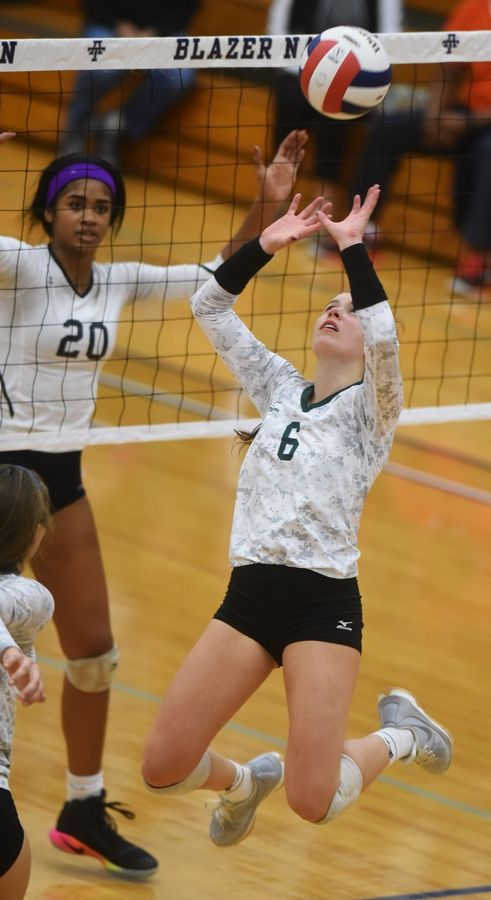 Glenbard West's Hannah Brodner leaves her feet to set the ball during the Class 4A Addison Trail volleyball sectional semifinal against Whitney Young Tuesday.