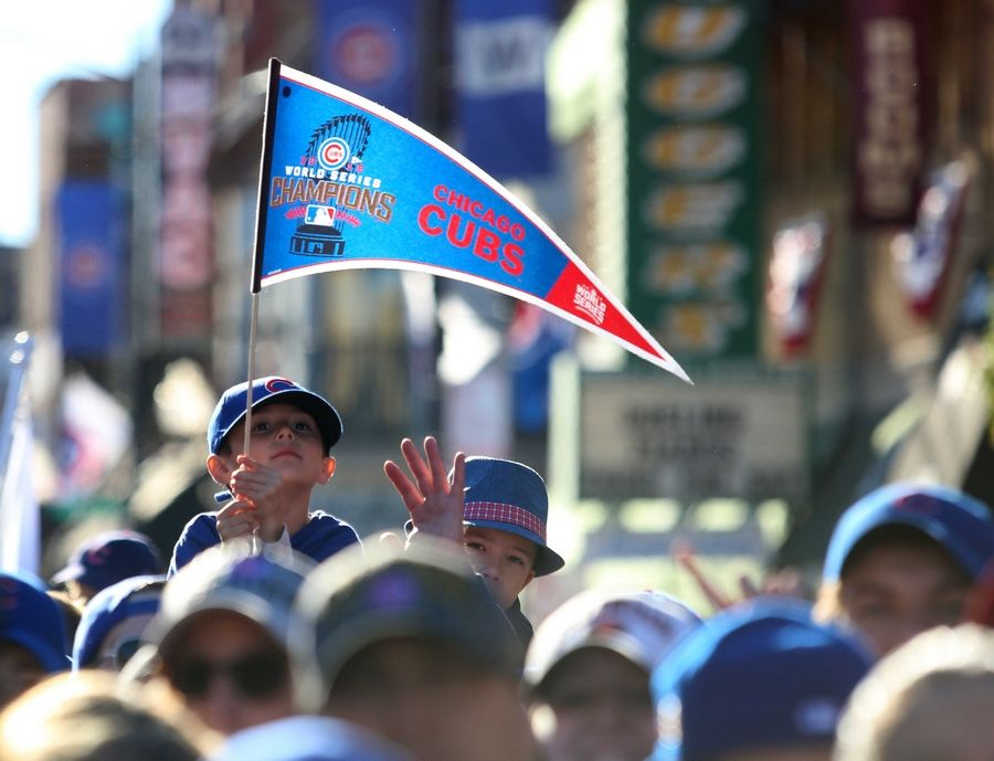 A youngster hoists a pennant as the World Series Champion Chicago Cubs parade begins at Wrigley Field Friday morning.