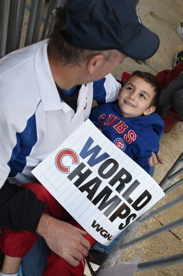 Eric Podgorski and his son Colin, 9, of Des Plaines relax as they wait for the parade to start. The Chicago Cubs celebrated their World Series win Friday with a parade that started at Wrigley Field and traveled down Michigan Avenue. The parade ended with a rally at Grant Park.