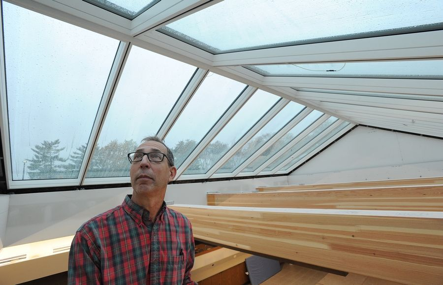 Jim Valentine, congregational operations officer for Our Saviour's Lutheran Church in Arlington Heights, looks over a new type of glass roof, the first of its kind. The glass is designed to change color electronically depending on the weather so that the temperature and lighting in the room are regulated automatically.