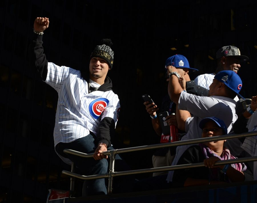 Infielder Javier Baez pumps his fist while riding a double-decker bus in the Chicago Cubs World Series Championship parade on Michigan Avenue Friday.