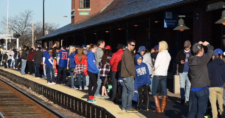 Cubs fans wait for a train Friday morning at the Arlington Heights Metra station on their way to the Cubs rally in Chicago.