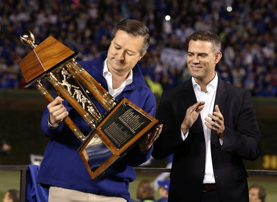 Chicago Cubs owner Tom Ricketts holds up trophy as president for baseball operations Theo Epstein watches after Game 6 of the National League baseball championship series against the Los Angeles Dodgers Saturday, Oct. 22, 2016, in Chicago. The Cubs won 5-0 to win the series and advance to the World Series against the Cleveland Indians.