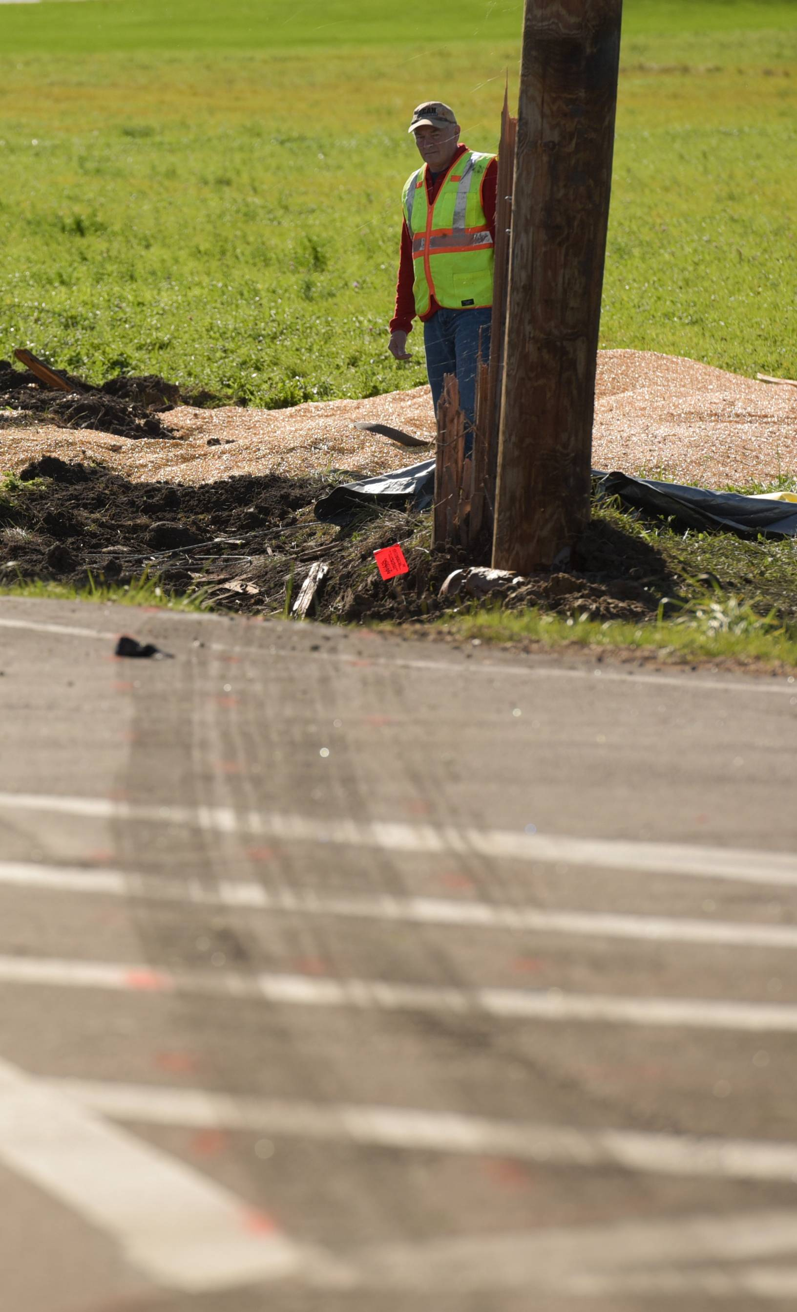 Skid marks lead off the road at the intersection of Meredith and Beith roads in Kane County as insurance investigator Jeffrey Golden of HRYCAY Consulting Engineers, Inc. surveys the scene of a crash that killed two teens Saturday.