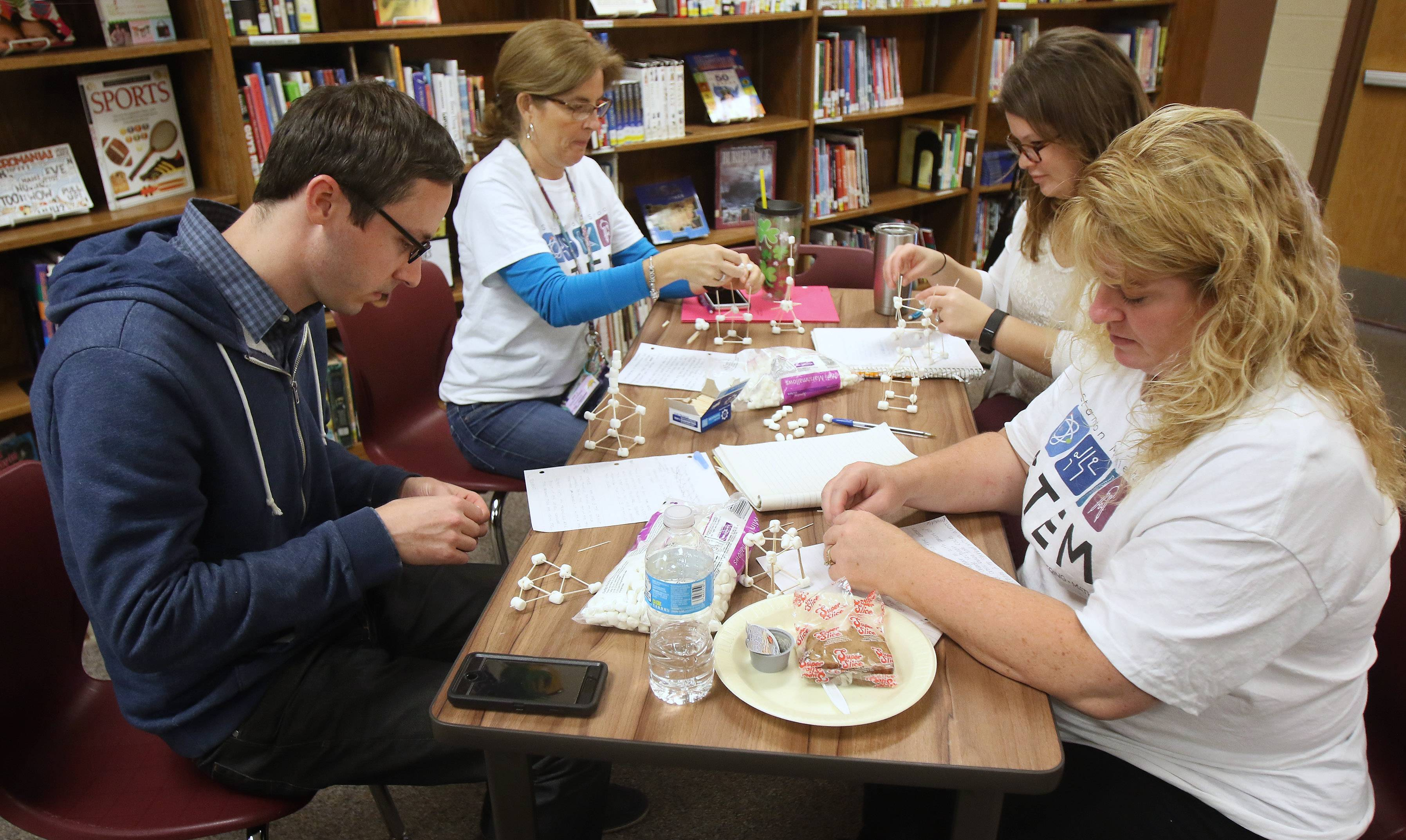 Teachers David Roat, left, Kathleen Winkiel, Donielle Williams and Colleen Hitzler build structures using toothpicks and marshmallows during a STEM workshop for teachers Monday at Stanton Elementary School in Fox Lake. Kristin Brynteson of Northern Illinois University's STEM program instructed the teachers with hands-on training and activities.