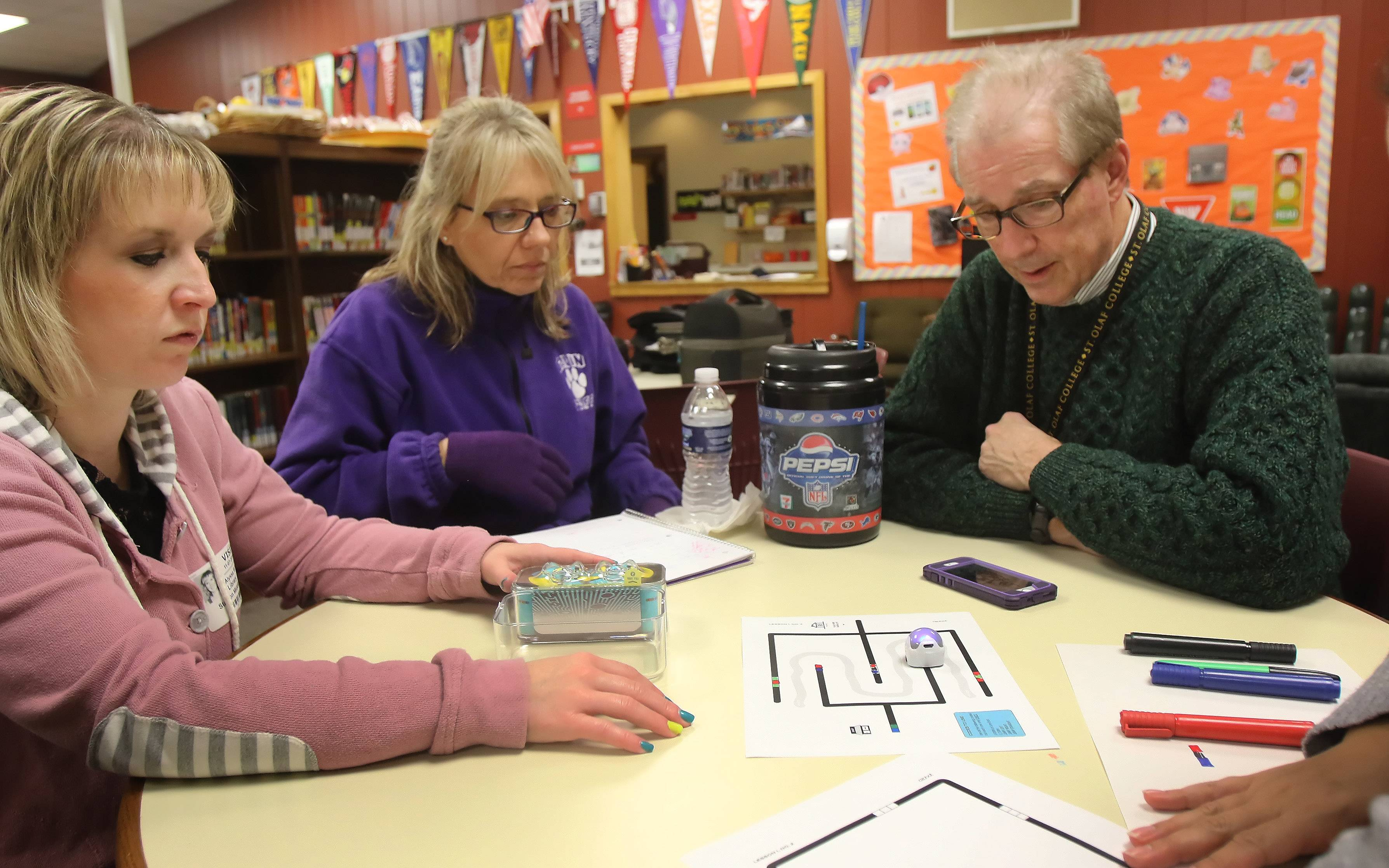 Teachers Alyssa Kay of Stanton School, left, Joanne Maher and Tom Gallagher of Gavin South Middle School work with an Ozobot during a STEM workshop for teachers Monday at Stanton Elementary School in Fox Lake. Kristin Brynteson of Northern Illinois University's STEM program instructed the teachers with hands on training and activities.