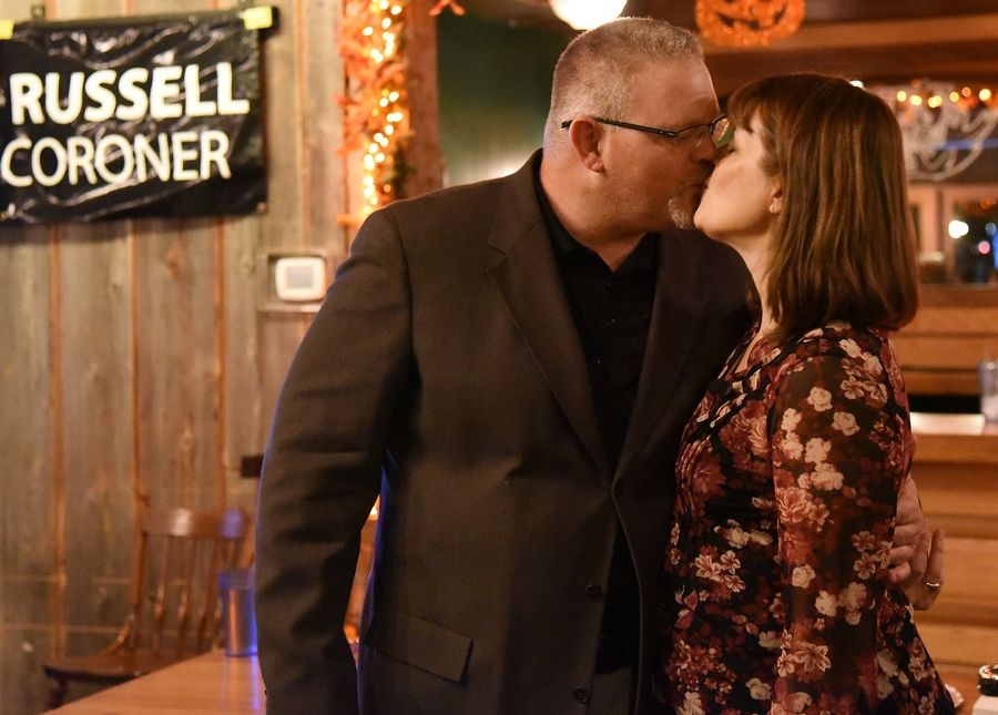 Rob Russell kisses his wife, Susan, after declaring victory in his race for Kane County Coroner during an election night gathering at Nick's Pizza & Pub in Elgin Tuesday.
