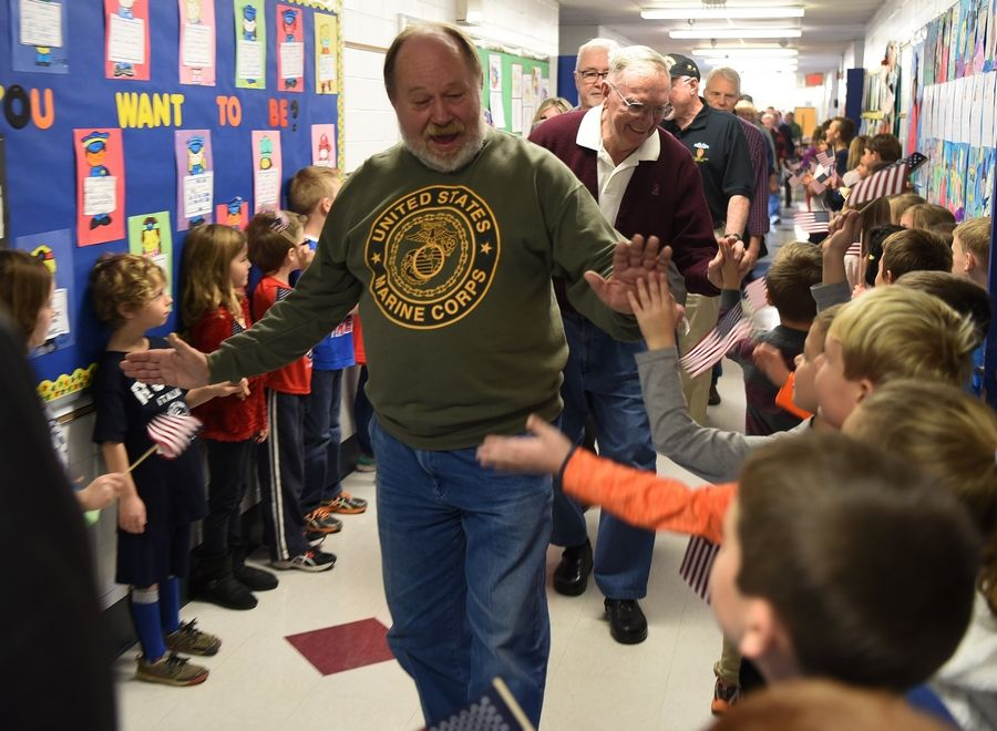 Marine Corps veteran Mel Rozanski of Arlington Heights is greeted by students Friday during a parade through the hallways of Windsor Elementary School in Arlington Heights.
