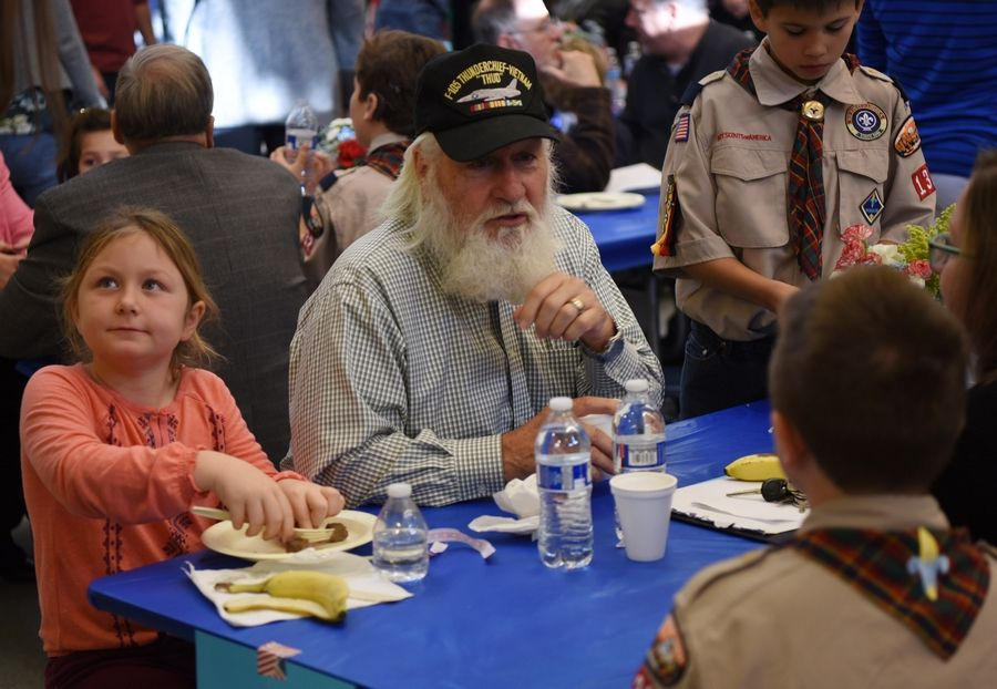 Second grader Hannah Tobin and her brother, Colin, a fifth grader, lower right, have breakfast Friday with their grandfather, Stephen Chapman of Huntsville, Alabama, during a Veterans Day event at Windsor Elementary School in Arlington Heights.