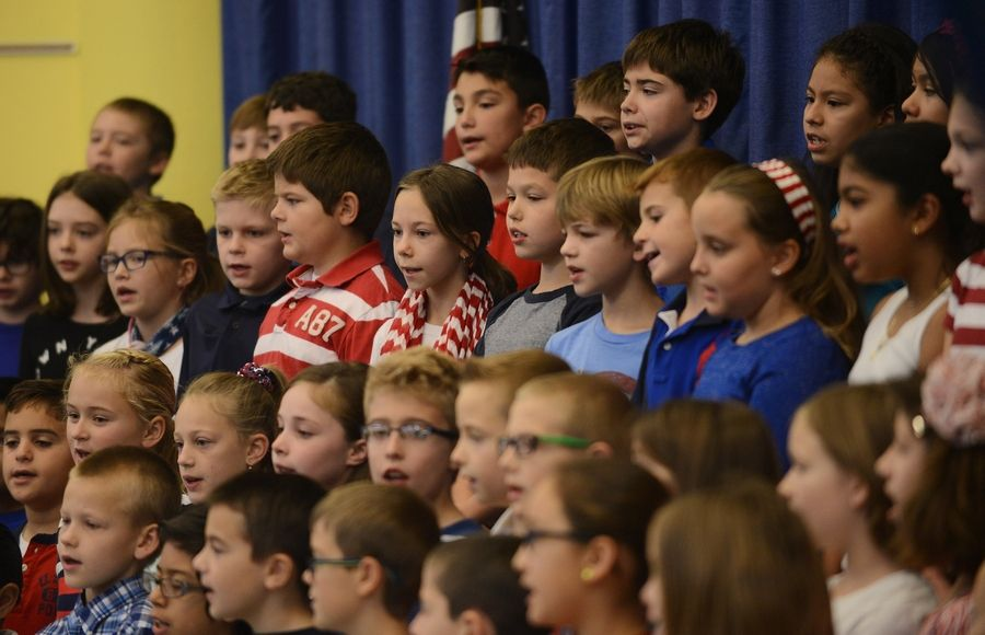 Students sing patriotic songs during a Veterans Day ceremony Friday at Windsor Elementary School in Arlington Heights.
