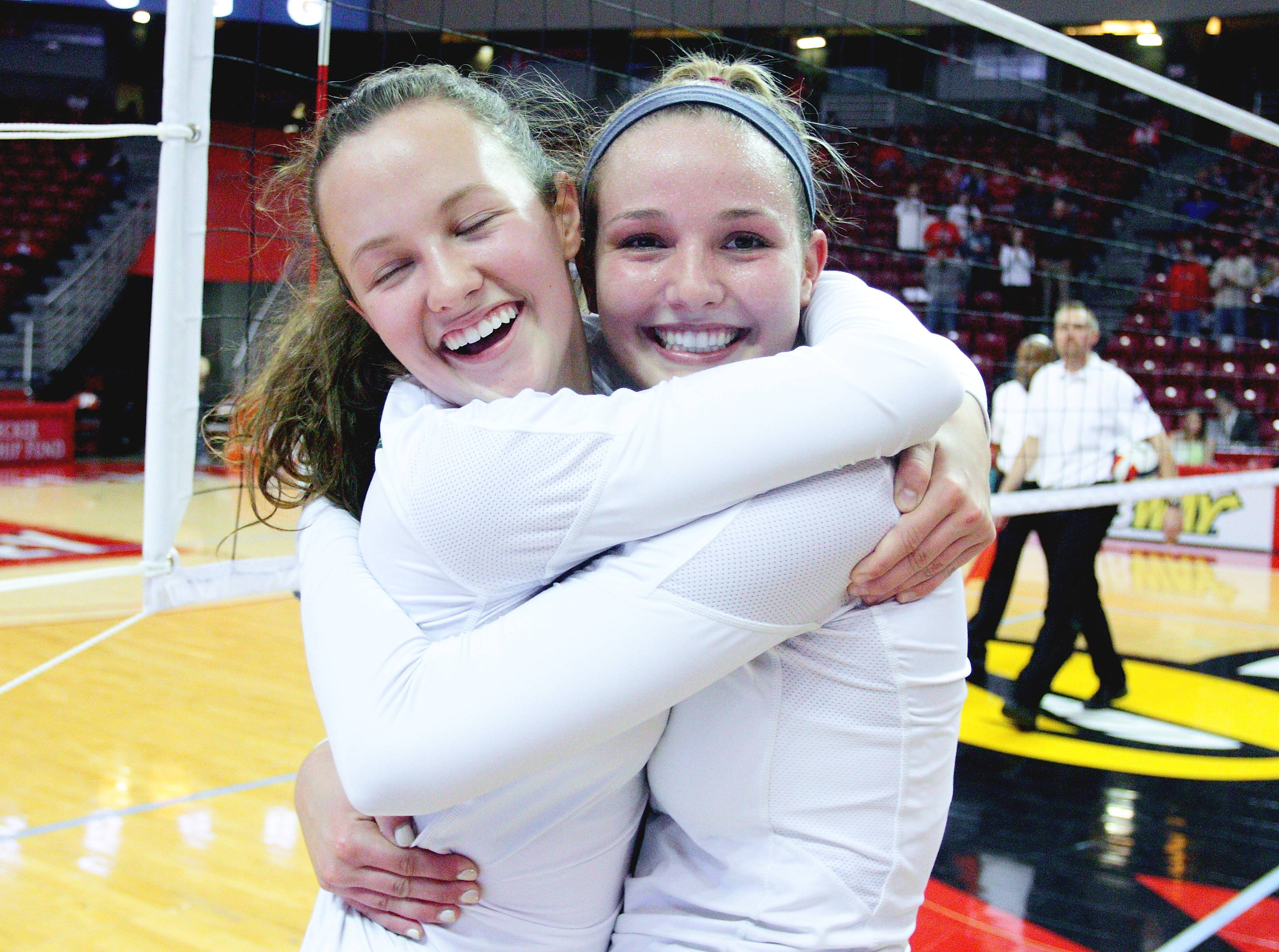 Stevenson's Sophie Sorenson and Jori Radtke embrace after their victory against Niles West in the Class 4A third-place game at Redbird Arena on Saturday. The Patriots won the third-place match over the Wolves 25-20, 21-25, 25-16.