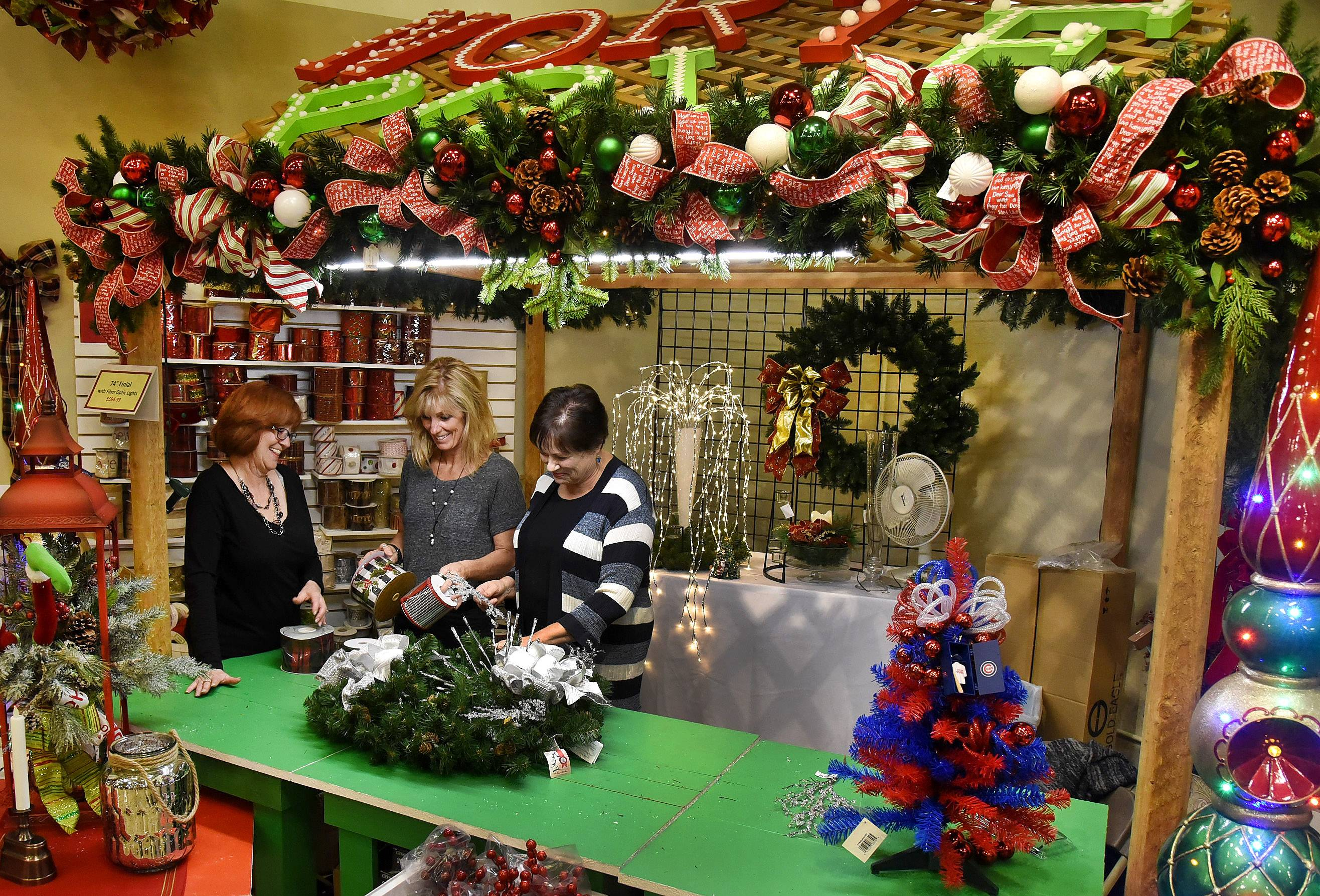 Show room manager Margie Smyth, from left, with designers Cassi Nickolas and Peg Fenstermaker go over some custom designs at Treetime Christmas Creations in Lake Barrington.