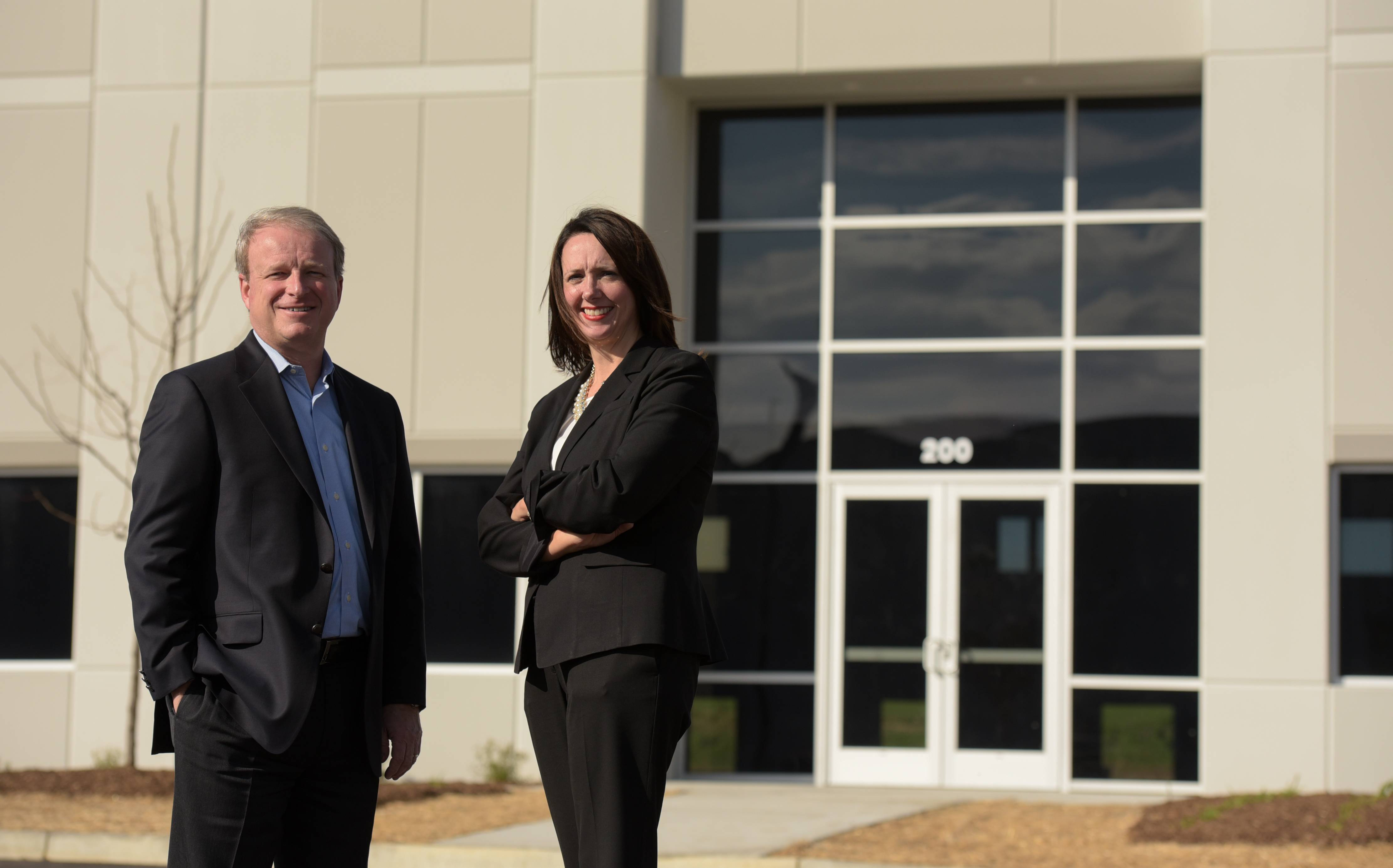 Don Schoenheider of Hillwood and Traci Buckingham Payette, senior vice president of CBRE, stand in front of the Romeoville Commerce Center buildings.