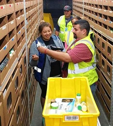 Amazon employees Dominic Lobono Sr., front right, and Sandra Limon pick the first customer order at Amazon's new Joliet fulfillment center. It was a pack of probiotic formula capsules shipped to a service member in the U.S. Air Force.