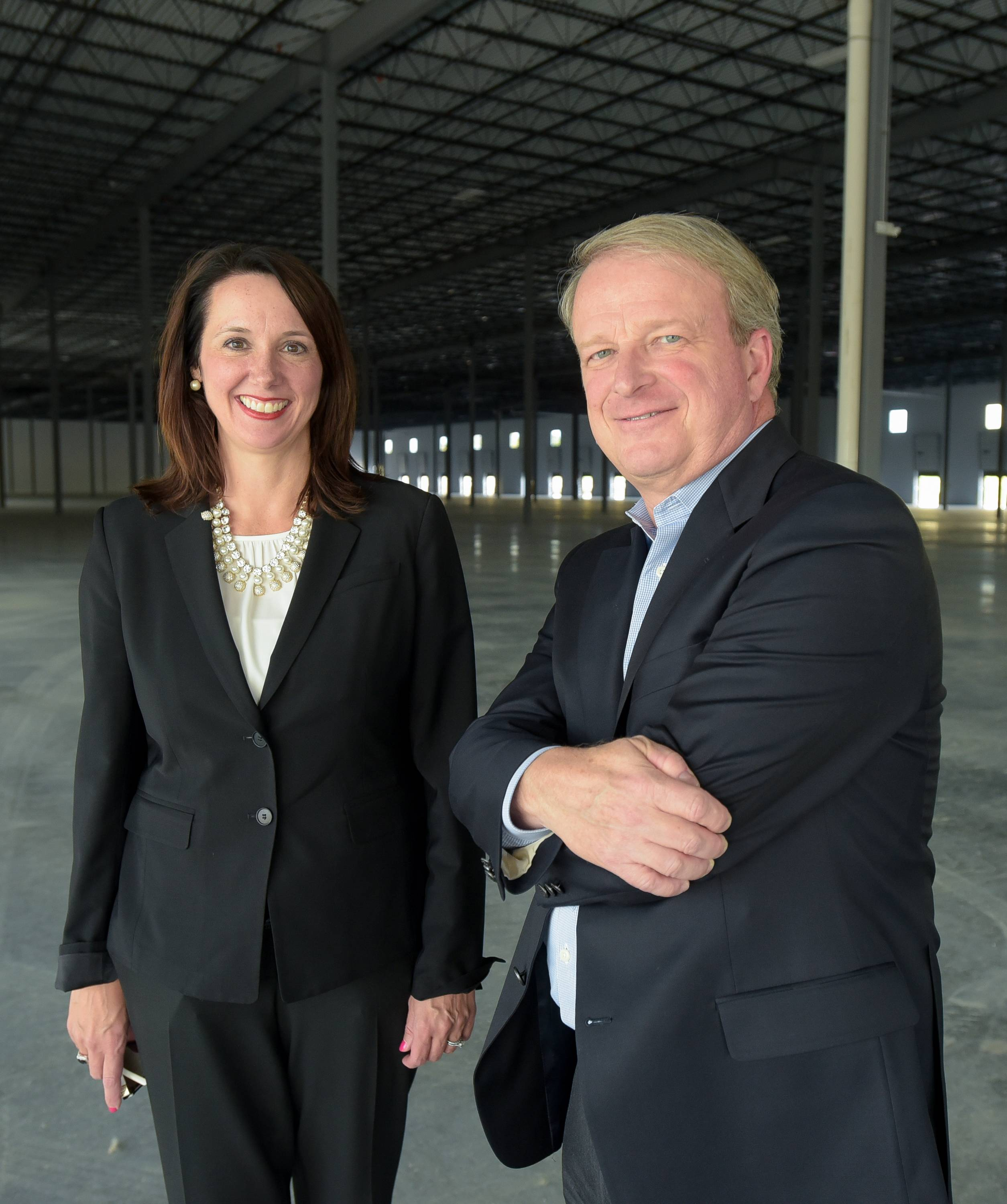 Traci Buckingham Payette, senior vice president of CBRE, and Don Schoenheider of Hillwood pose in a Romeoville Commerce Center building.