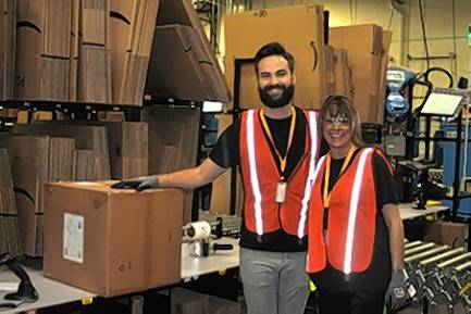 Employees John Walles and Lisa Coffey at Amazon's new Romeoville fulfillment center prepare the first customer order from the facility, a set of decorative cylinder planters, shipped to a customer in Naperville.