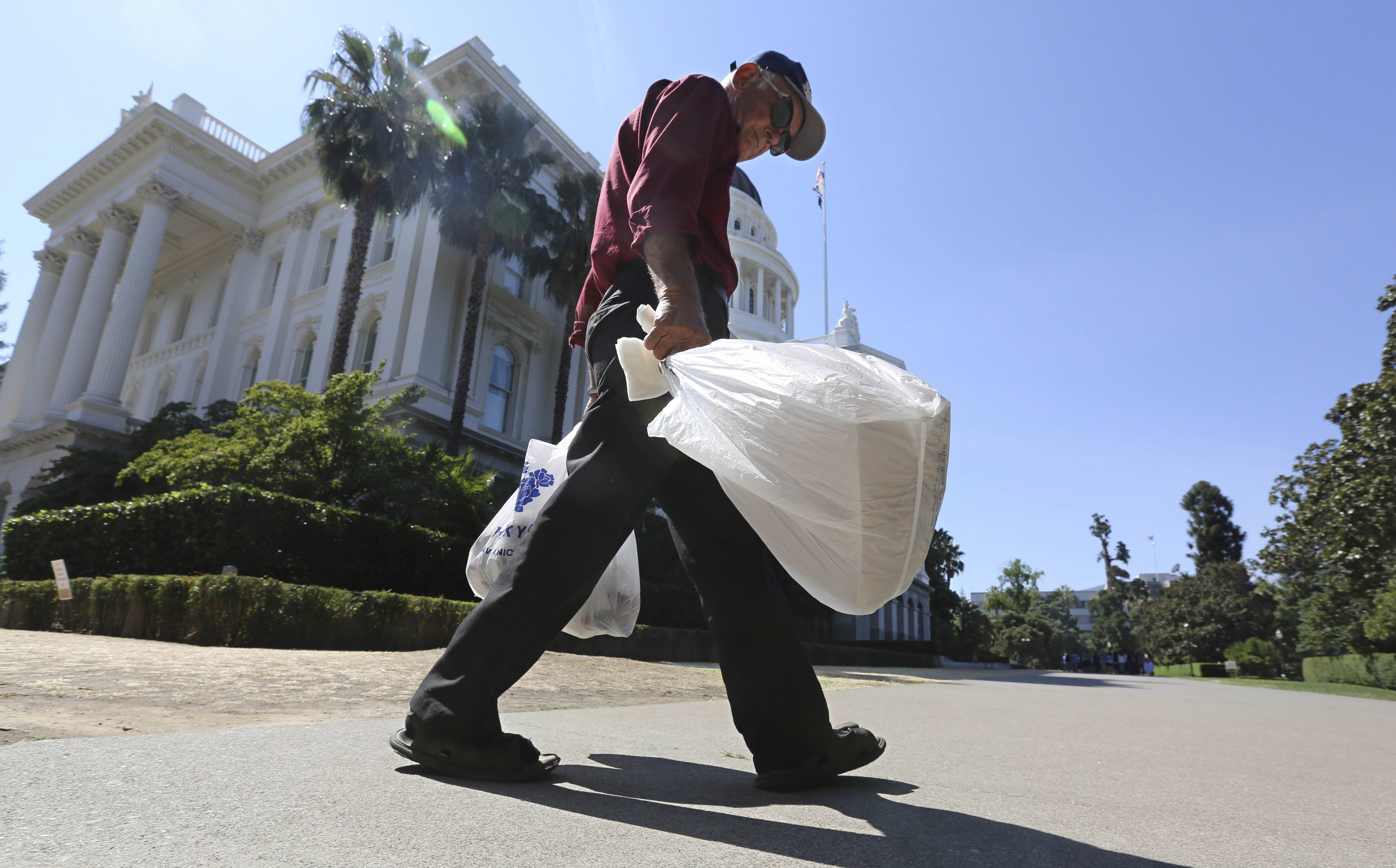 A man carries single-use bags in Sacramento, California. Voters in California last week affirmed a ban on such bags.