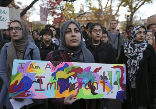 A student holds a sign as she joins a large crowd gathered to protest some of President elect Donald Trump policies and to ask school officials to denounce his plans at Rutgers University Wednesday, Nov. 15, 2016, in New Brunswick, N.J. College students at campuses around the United States say they are planning rallies and walkouts to call on school administrators to protect students and employees against immigration proceedings under Donald Trump's presidency.