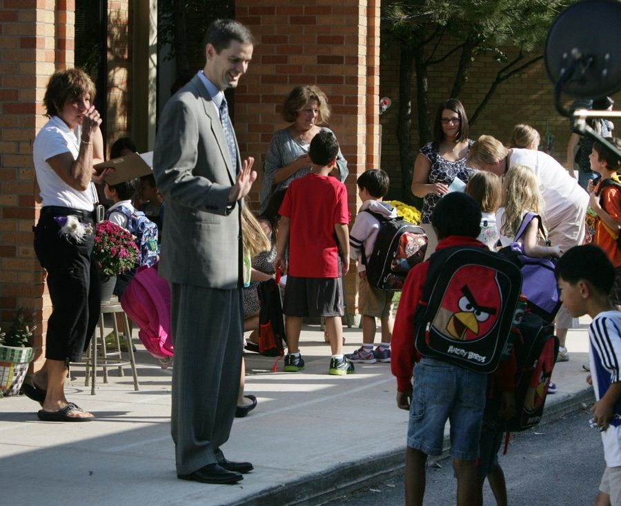 Superintendent Scott Warren greets children at Laura B. Sprague School in Lincolnshire on the first day of classes in 2012. Warren said the elementary school district is nearing a decision on changing start times for its youngest and oldest students.