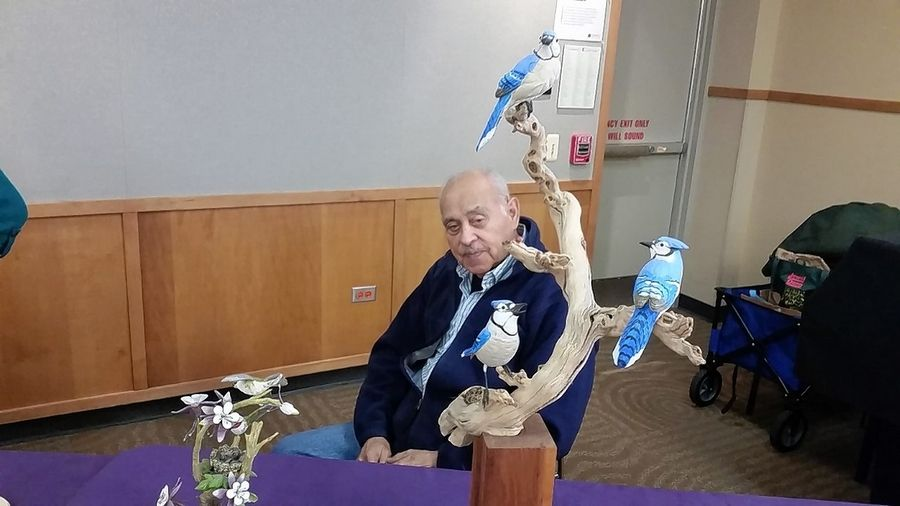 Jesse Ruiz sits near a statue he made of three blue birds at an event hosted by the North Suburban Woodcarvers organization in Lake Zurich on Saturday.