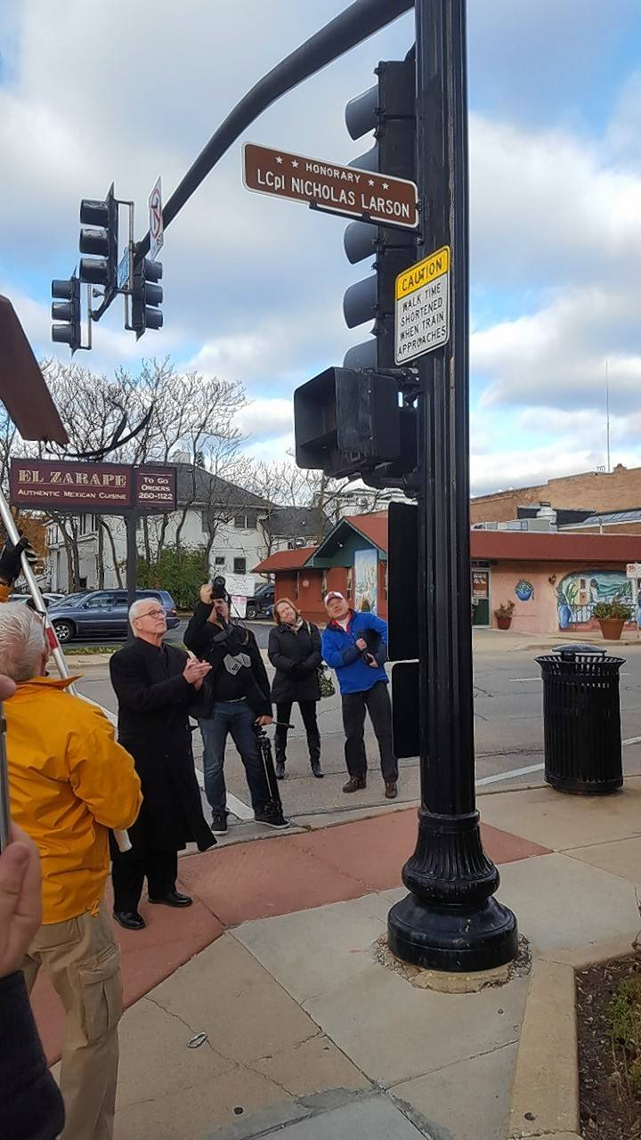 Community members gather Saturday afternoon to see an honorary street sign for U.S. Marine Lance Cpl. Nicholas Larson unveiled at the southwest corner of Front and West streets in Wheaton. Larson, a 2003 Wheaton North High School graduate, was killed in Iraq in 2004.