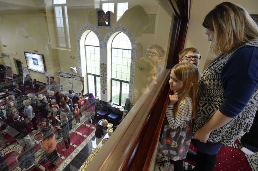 Gina Intoppa and her children, Giuliana, 5, and Luca, 8, look over the hundreds of people streaming into the Midwest Islamic Center near Schaumburg, which opened its doors to visitors for a special presentation Saturday.