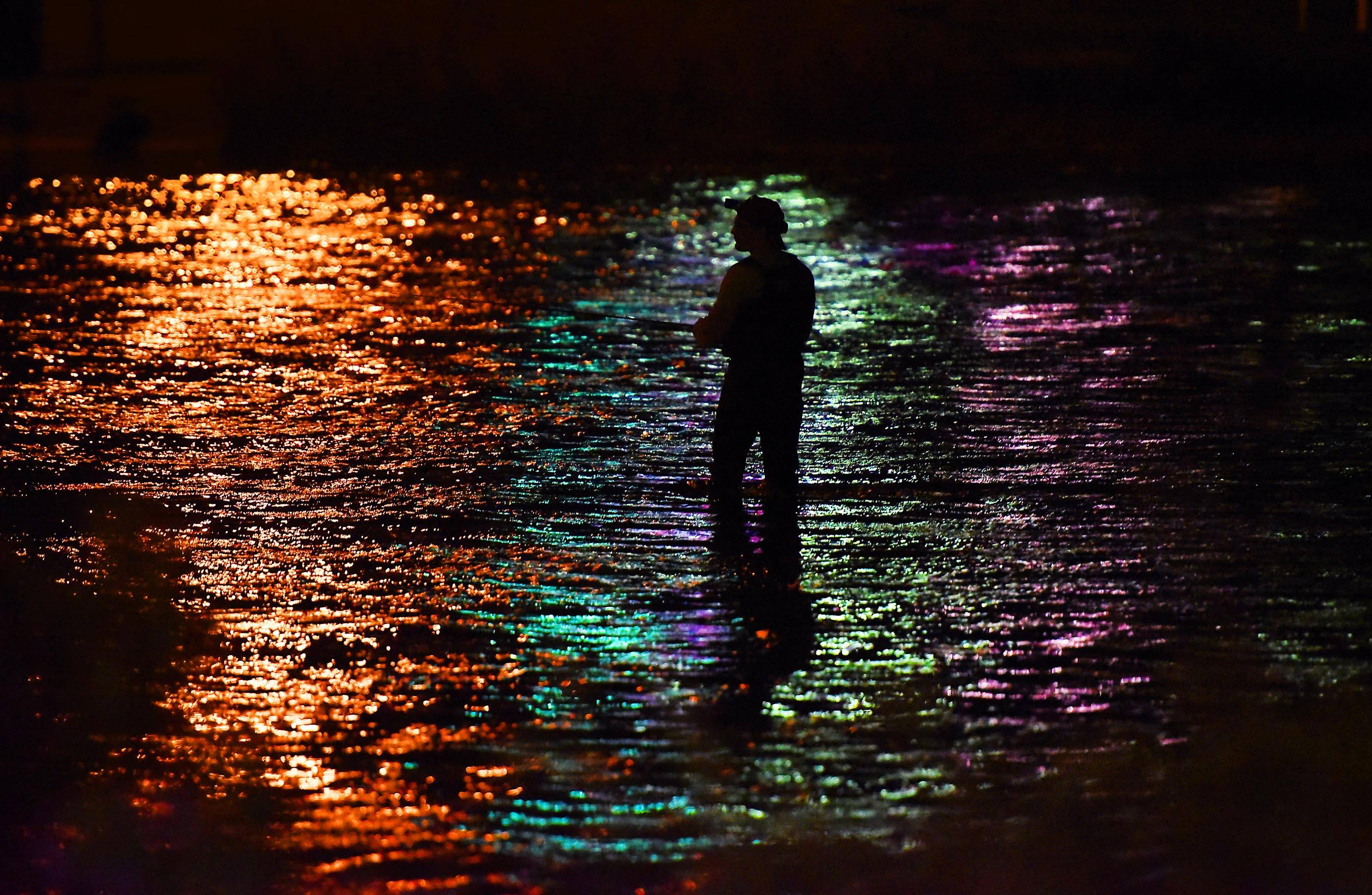A fisherman wades in the Fox River and fishes by the light of passing cars, business signs and street lights in South Elgin Thursday evening.