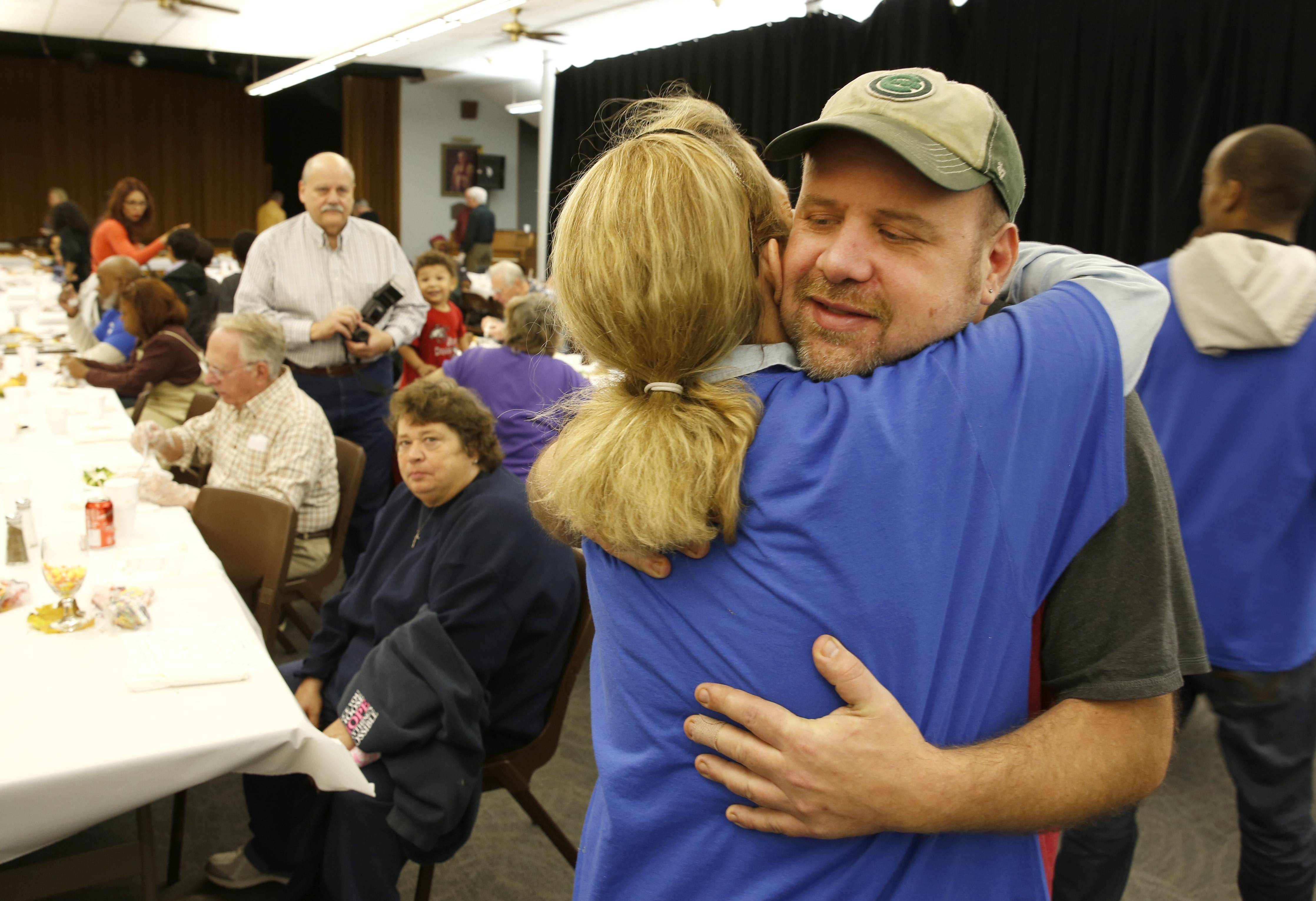 Jeff Turner, owner of In The Neighborhood Deli in Elgin, gets a hug of thanks from Theresa Boswell of Elgin, during a Thanksgiving Day celebration for the community at the First United Methodist Church in Elgin. Turner organized the event and Boswell was one of numerous community volunteers.