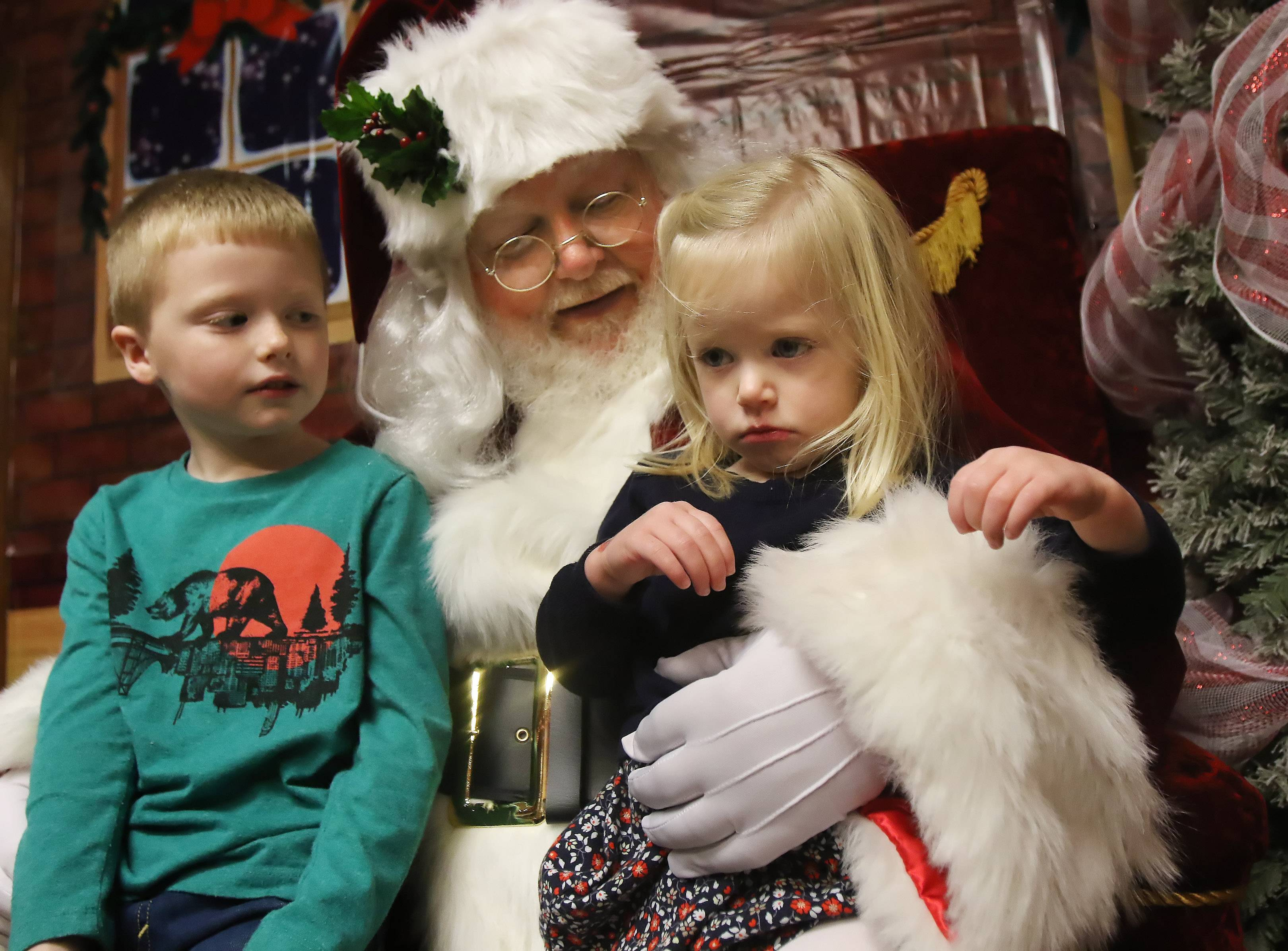 "Gilbert R. Boucher II/gboucher@dailyherald.comTwo-year-old Clara Osowski of Mount Prospect is unhappy as she sits on Santa's lap with her brother, Caden, 5, at Santa's Frozen Village in downtown Antioch Sunday. Children met with Santa Claus as well as Elsa and Olaf, characters from the movie ""Frozen,"" while touring the winter wonderland. Santa is Alan Bednar of Antioch who has been playing him in the village for 29 years."