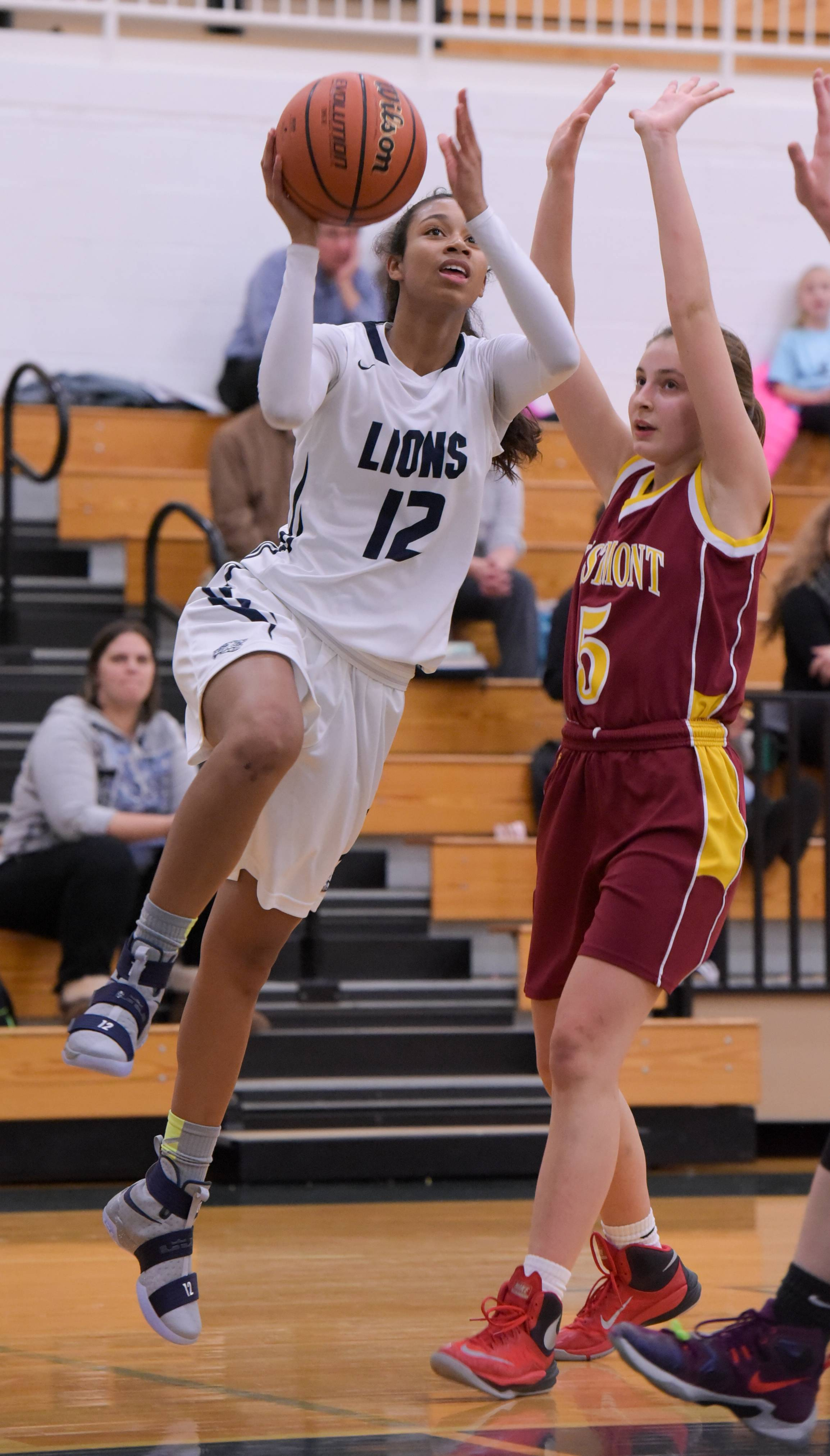 Lisle's TyAnn Legrand-Melton lays up for a shot past Westmont's Sydney Pardy during girls varsity basketball action Monday in Lisle.
