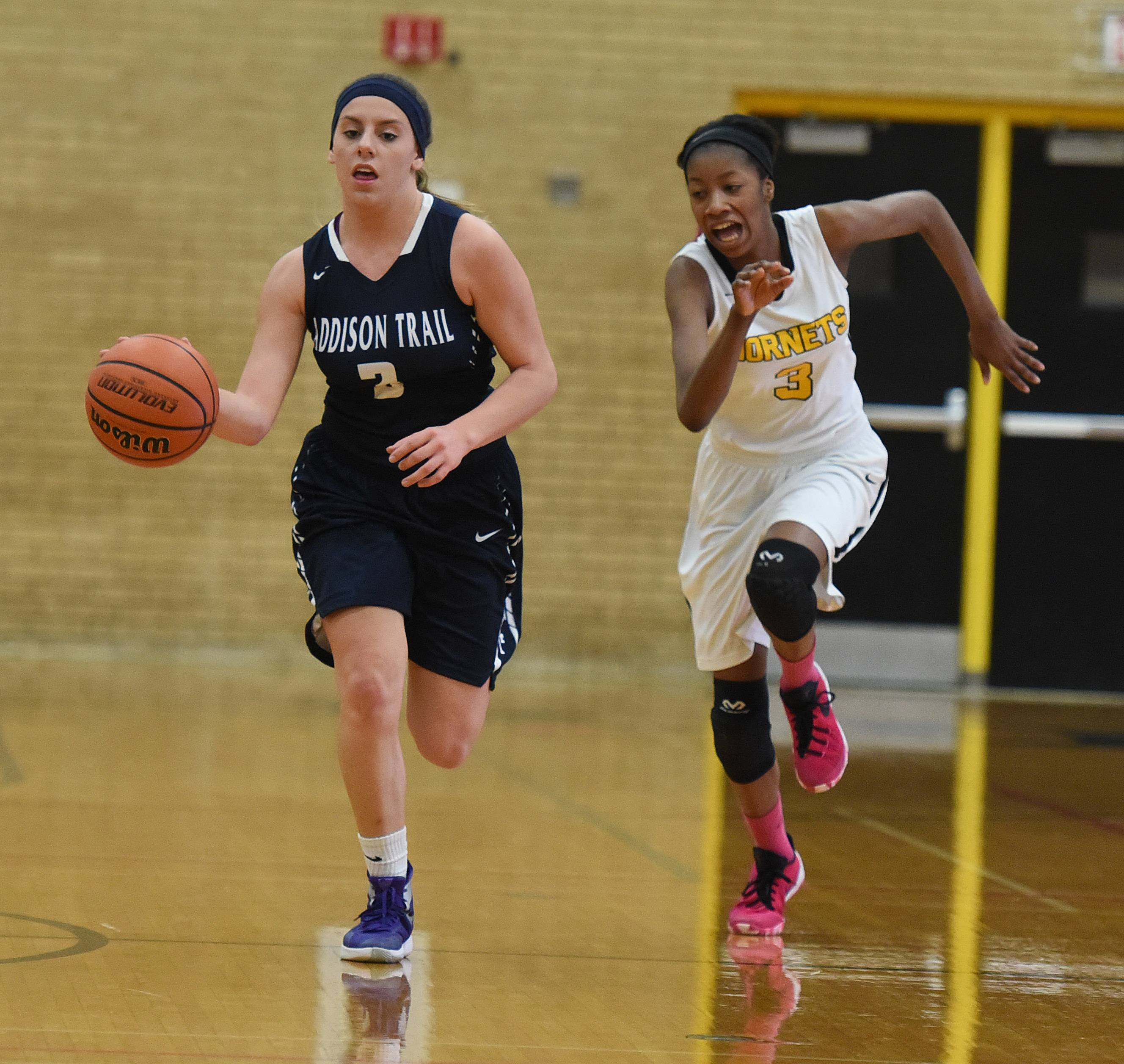 Nicci Scorza of Addison Trail moves the ball as Hinsdale South's Evelyn Edmond (3) chases.