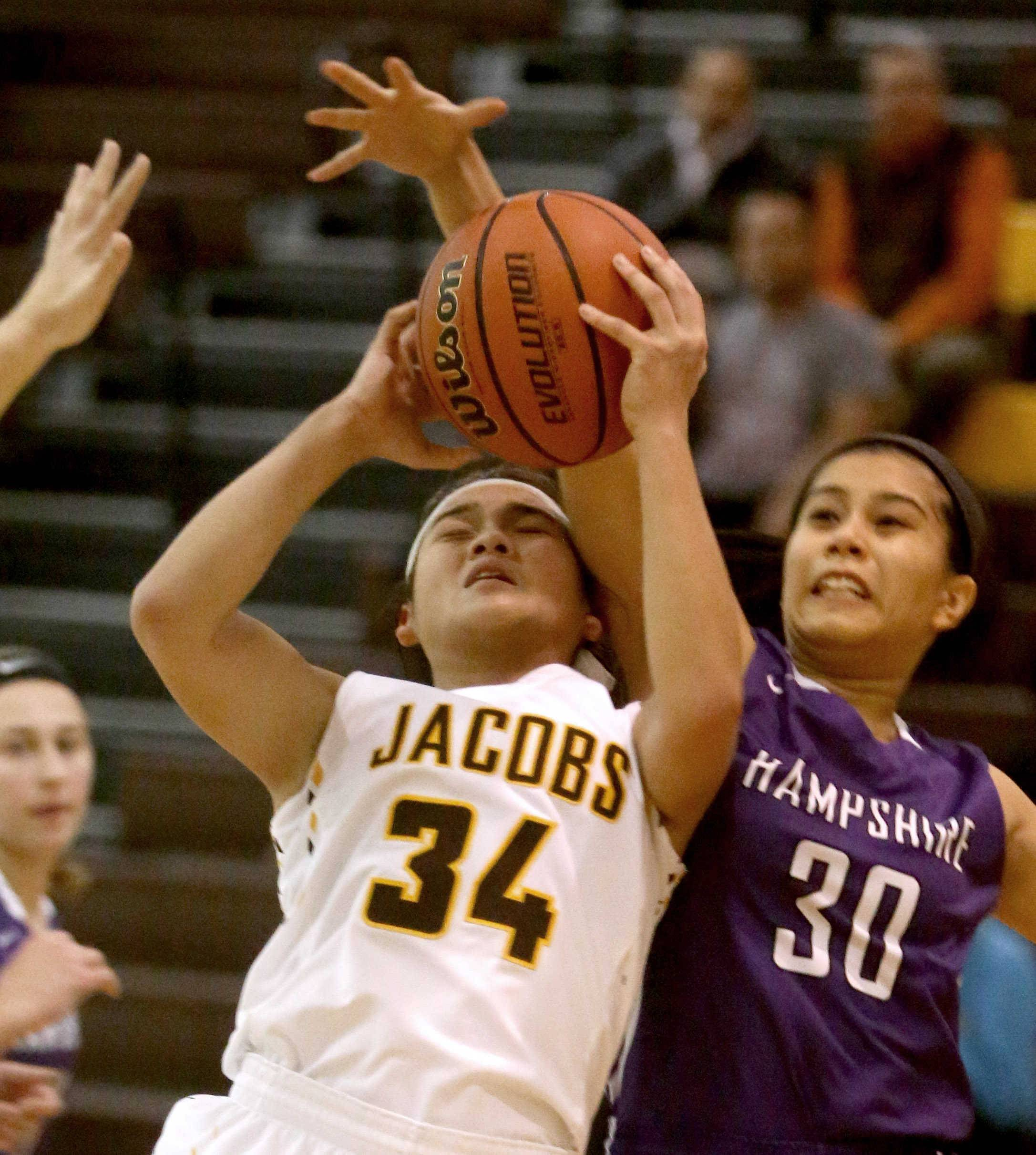 Hampshire's Kiera Guerrero-Gay, right, battles Jacobs' Kyra Cabusao, left, during varsity girls basketball action in Algonquin Tuesday night.