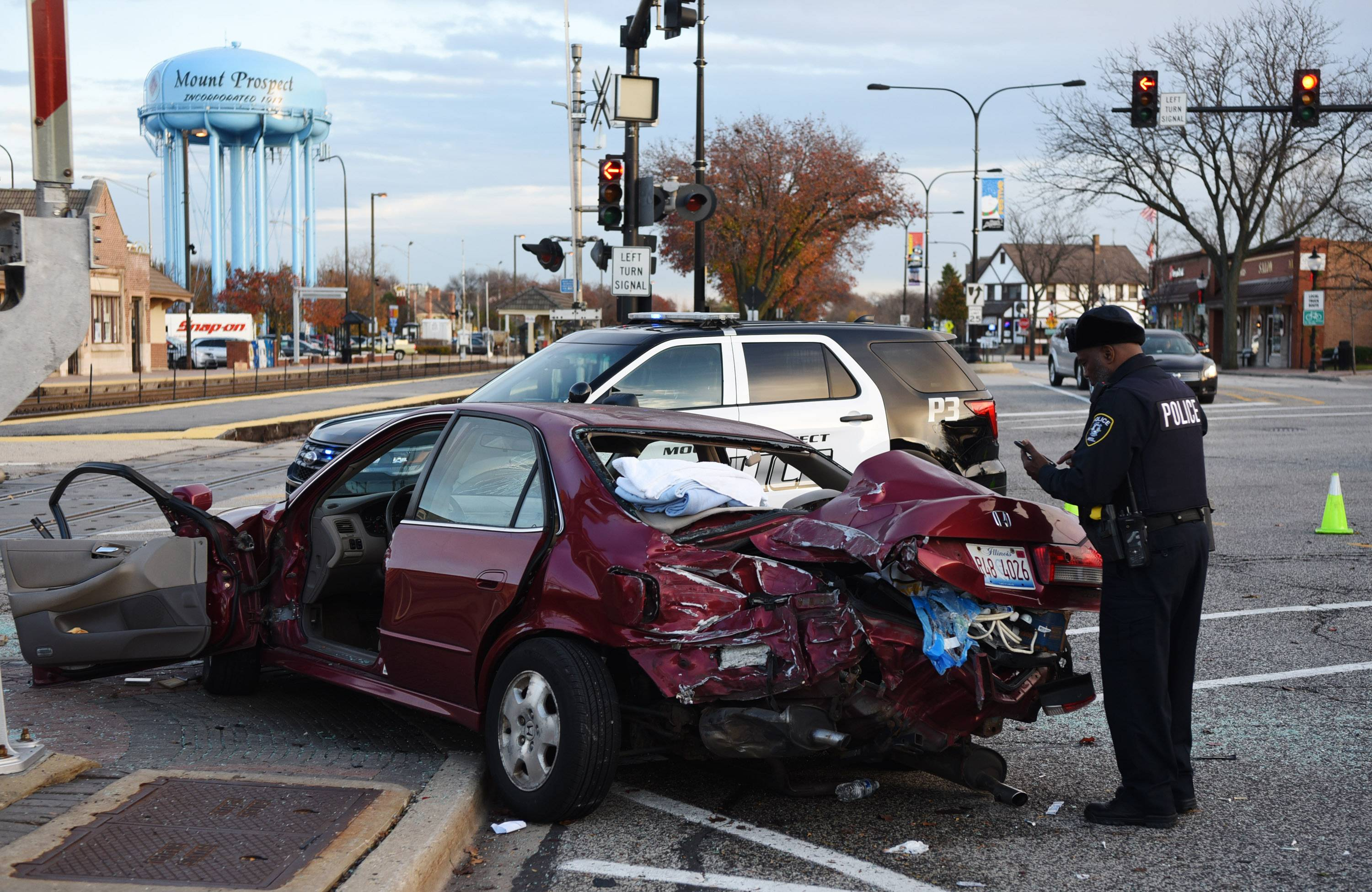 A Metra police officer views a damaged Honda sedan Tuesday after it was struck by a freight train at the intersection of Main Street and Prospect Avenue in Mount Prospect. The driver had to be cut from the car but appeared uninjured.