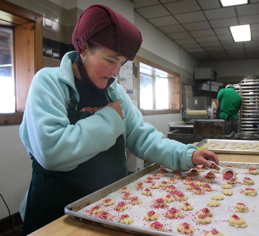 Lambs Farm resident Jen Hart put sprinkles on Lambs Farm Famous Butter Cookies in the bakery near Libertyville on Wednesday. The cookies will be sold at the 36th Annual Lambs Farm Holiday Lights, Gift & Craft Fair this weekend at Arlington Park.