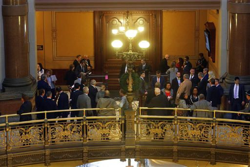 "Lawmakers, lobbyist and visitors stand along the ""Brass Rail"" outside the House chambers during veto session at the Illinois State Capitol Thursday, Dec. 1, 2016, in Springfield, Ill."