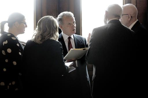 Illinois Speaker of the House Michael Madigan, D-Chicago, center, talks with staff members and Illinois Rep. Greg Harris, D-Chicago, far right, inside Illinois Gov. Bruce Rauner's office during veto session at the Illinois State Capitol Thursday, Dec. 1, 2016, in Springfield, Ill.