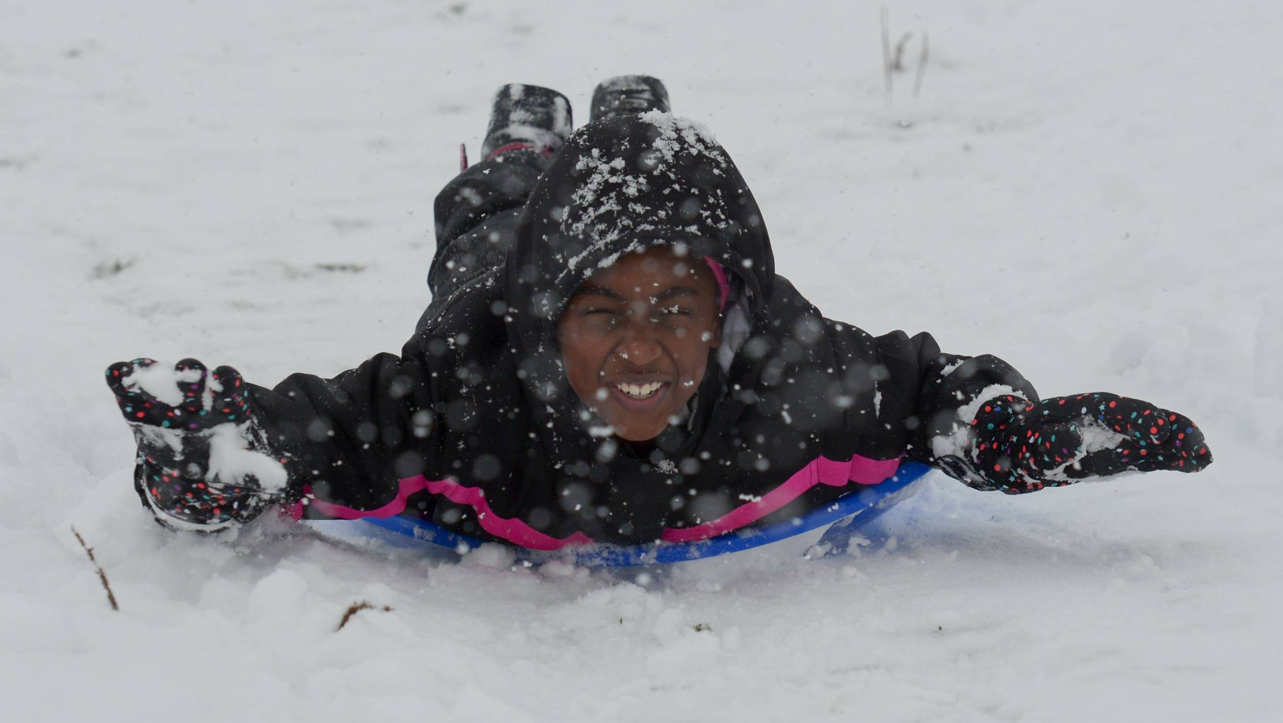 Aaliyah Cage, 9, of Hanover Park slides down the sledding hill Sunday at Community Park in Hanover Park during the first snowfall of the season.