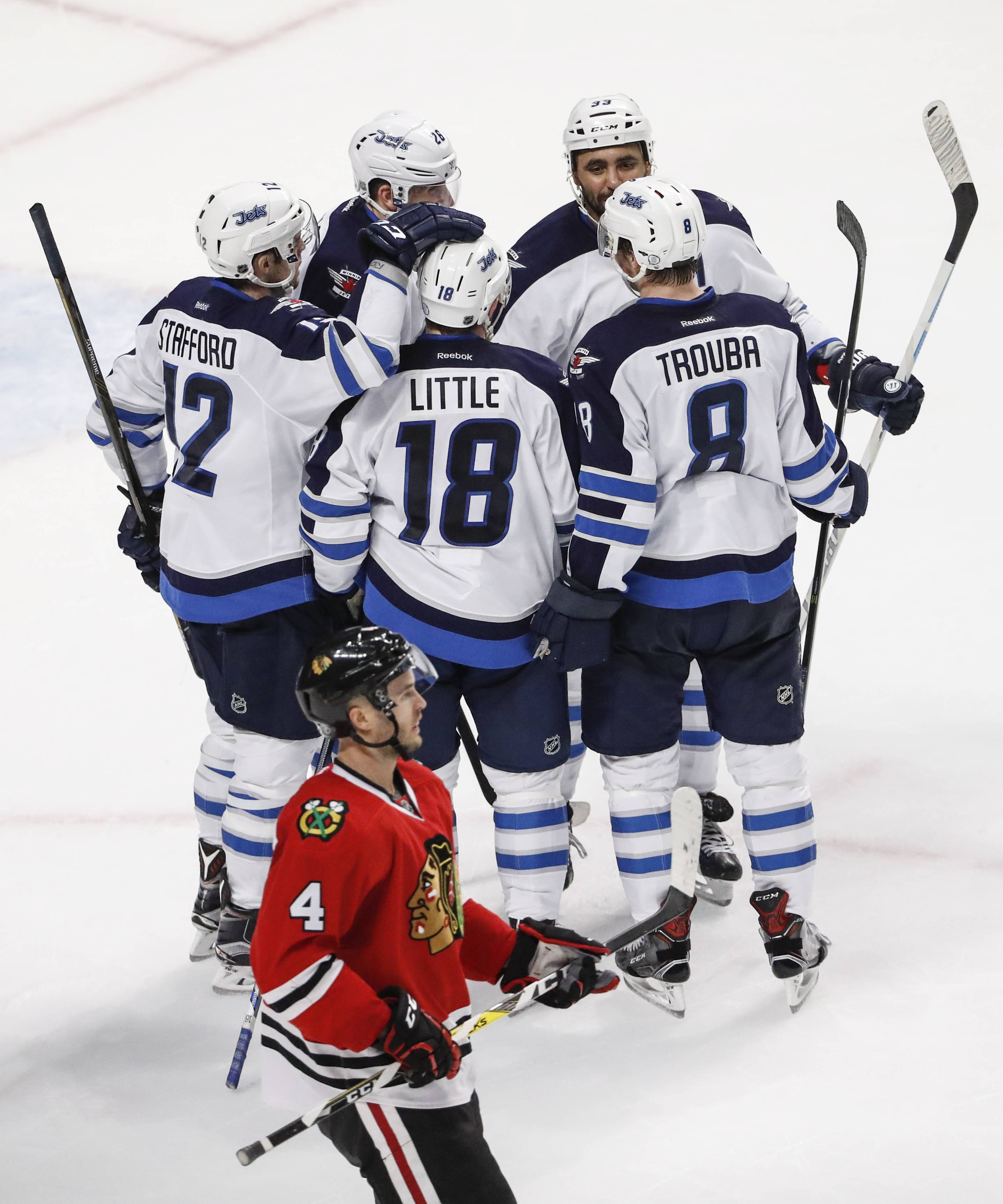 Winnipeg Jets center Bryan Little (18) celebrates with teammates after scoring against the Chicago Blackhawks during the second period of an NHL hockey game, Sunday, Dec. 4, 2016, in Chicago.
