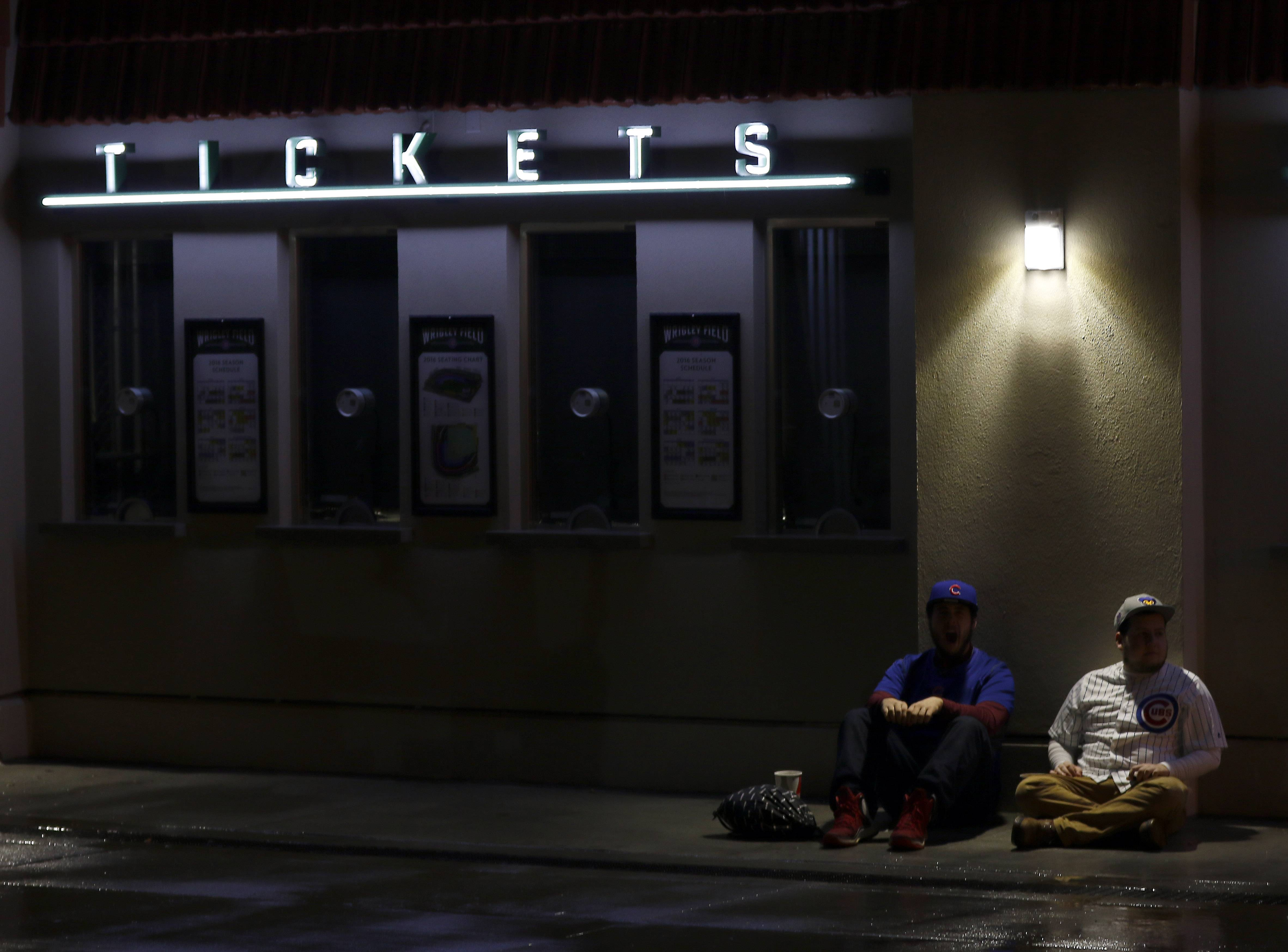 Two fans sit outside the ticket windows at Wrigley Field on Nov. 2 as the Chicago Cubs play World Series Game 7. The Chicago Cubs said Monday that ticket prices are rising 6 percent to 31 percent for 2017.