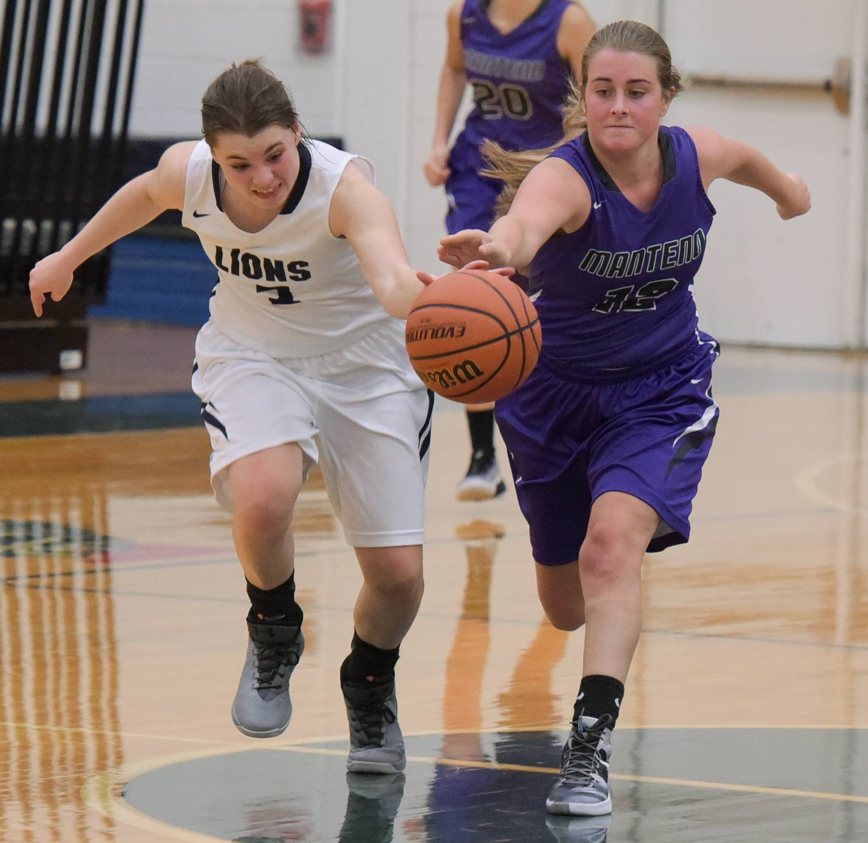 Lisle's Natalie Takahashi and Manteno's Cam Renchen scramble for a loose ball.