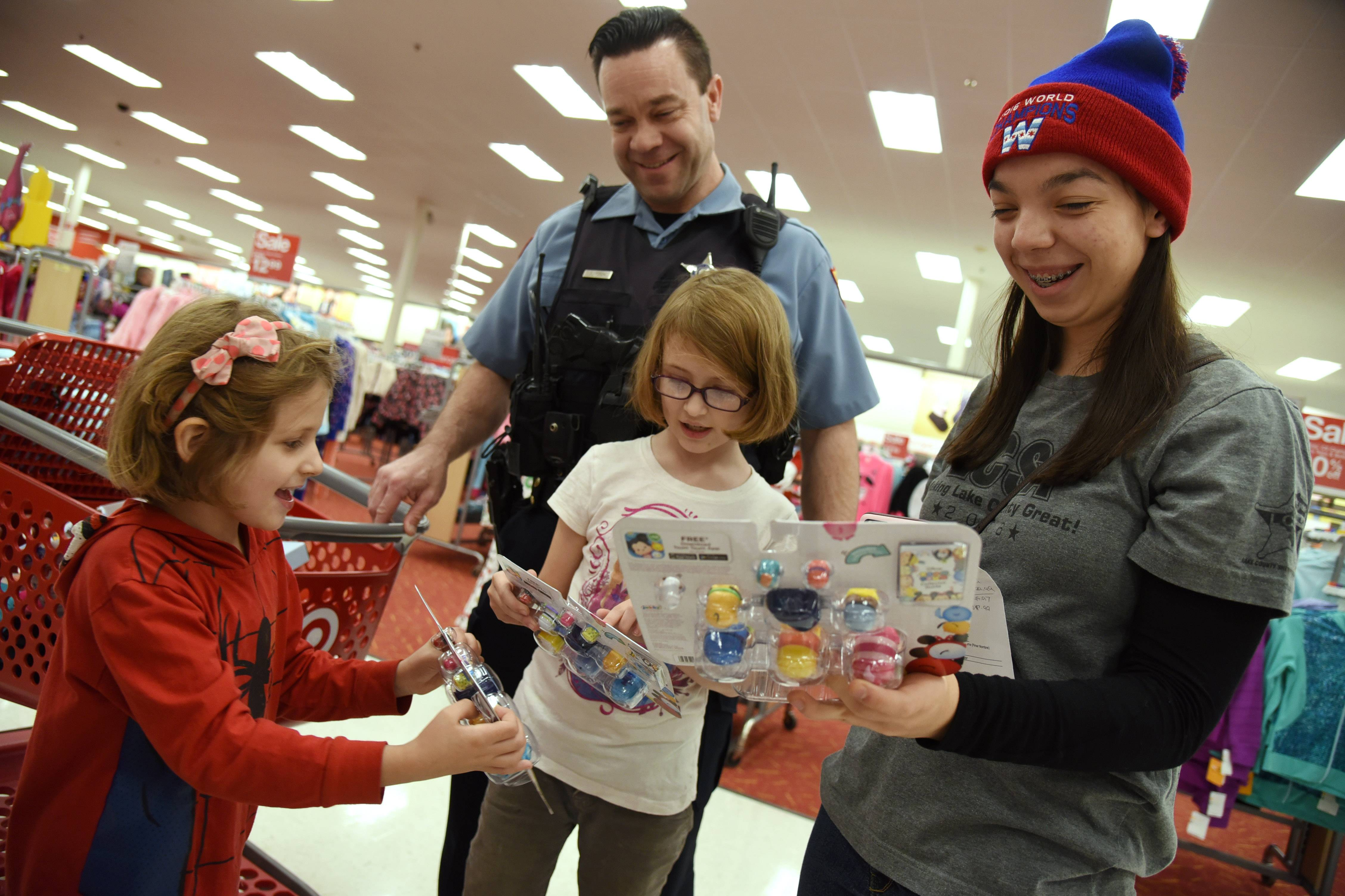 "Lake County Sheriff's Deputy Tim Fitch is assisted by his daughter Paige Fitch, right, as they spend time with Alice Hale, 6, left, and sister Anne Marie Hale, 9, both of Winthrop Harbor, during Tuesday's ""Shop with a Sheriff"" at the Mundelein Target."