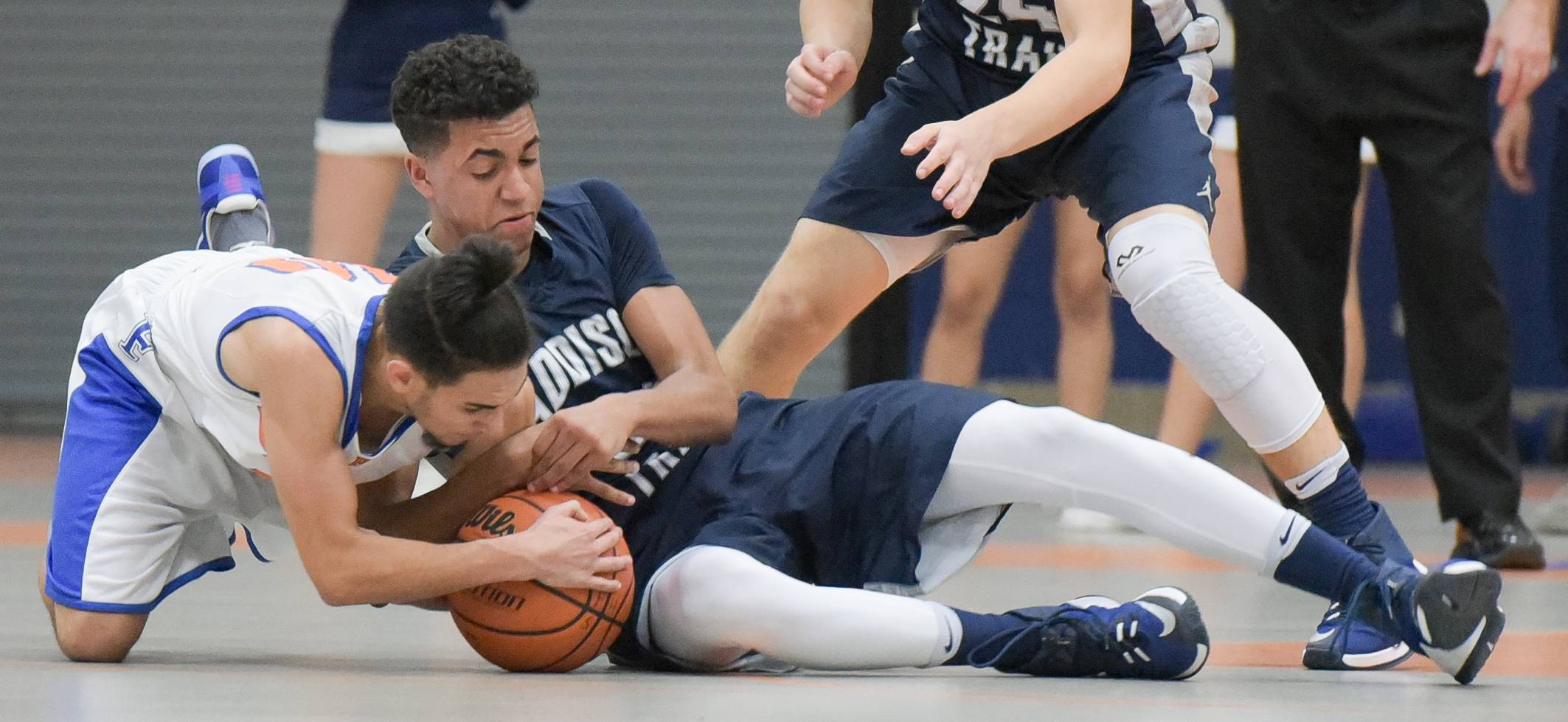 Fenton's Bryan Andrade and Addison Trail's Michael Williams struggle for control of the ball during varsity boys basketball in Bensenville Monday.