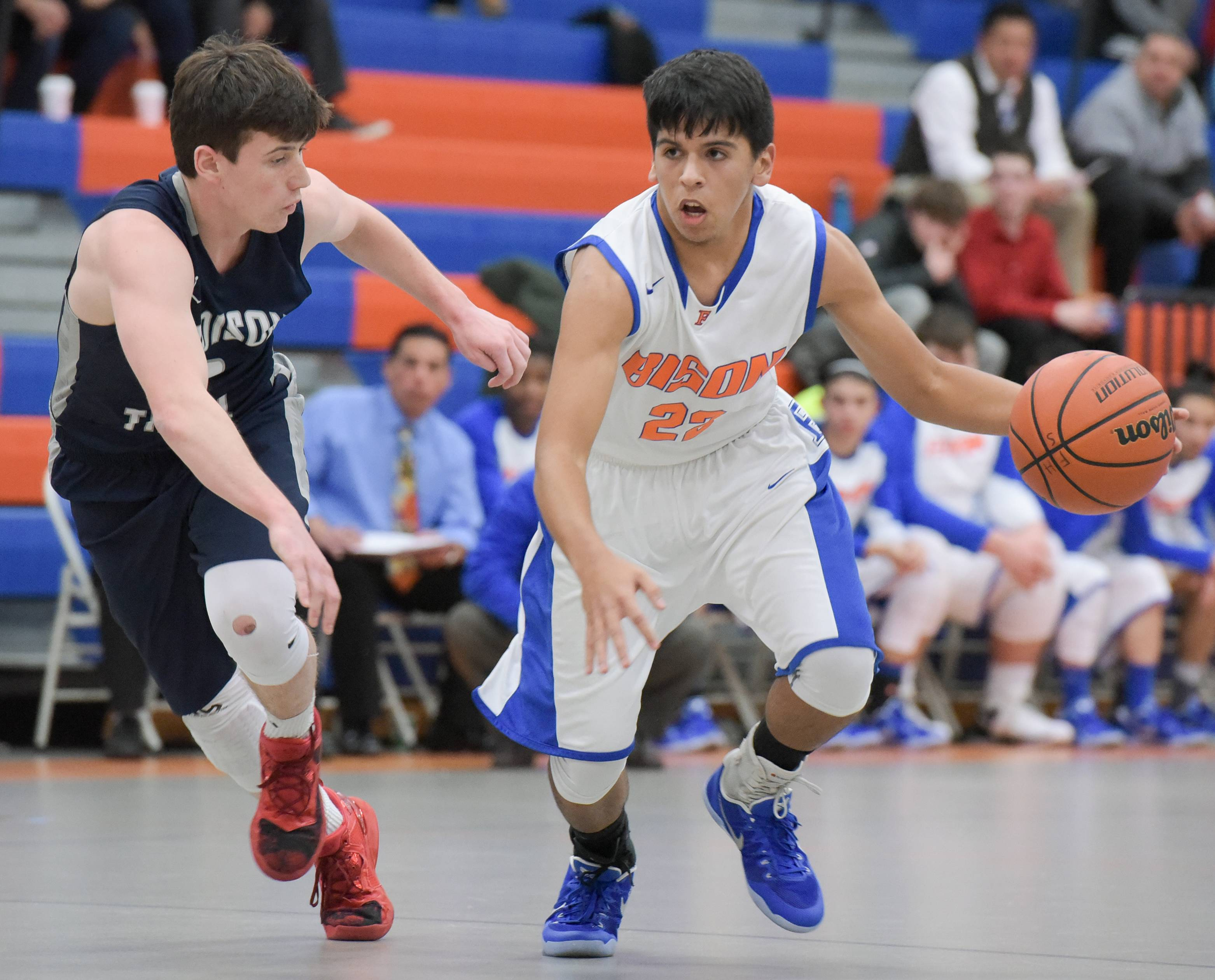 Addison Trail's Jack Kalbas keeps pace with Fenton's Javier Sanchez during varsity boys basketball in Bensenville.
