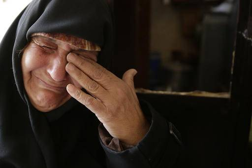 In this Sunday, Dec. 4, 2016 photo, Amina Hamawy cries after she returned to her looted home in the Hanano district of eastern Aleppo, Syria. It's a painful homecoming shared by hundreds of Syrians who are returning to areas devastated by years of war and then retaken from the city's embattled rebels in a recent government offensive. More than 30,000 people have fled Aleppo since the latest government offensive began last month, joining the more than 10 million Syrians -- nearly half the population -- who have fled their homes since the conflict began. (AP Photo/Hassan Ammar)